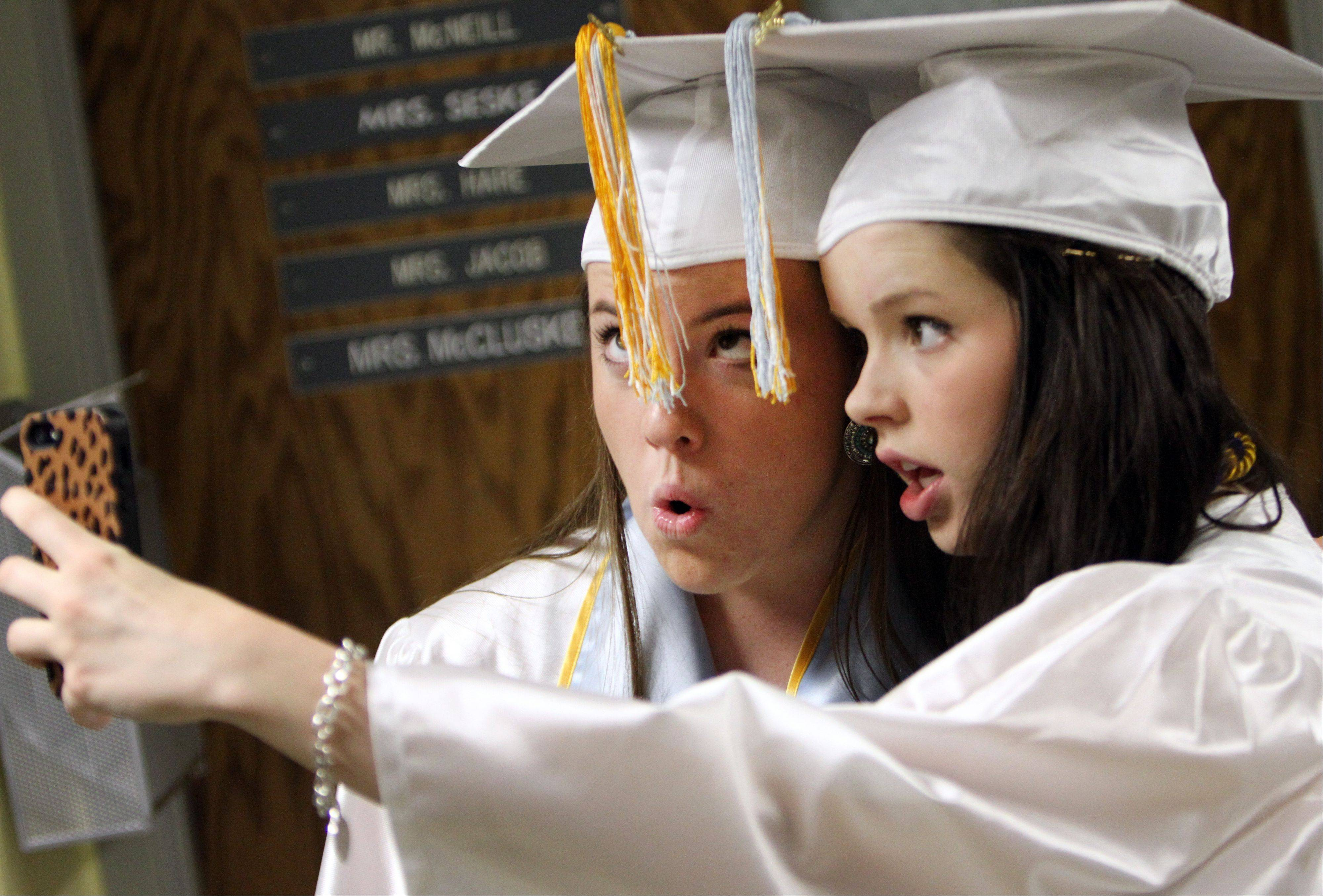 Renee Pond, left, and Margaret Dugan make funny faces as they pose for a picture during graduation ceremonies Sunday at Maine West High School.