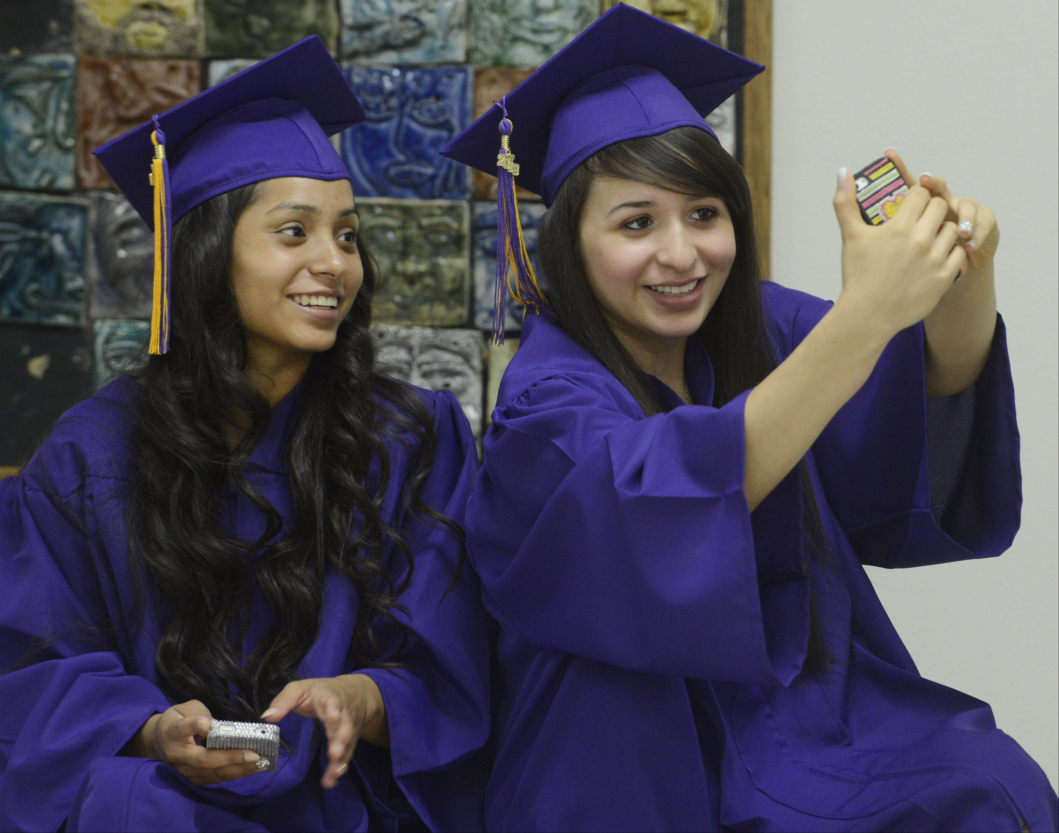 Guadalupe Flores, right, takes a photo of herself with friend Sury Rodriguez prior to the Rolling Meadows High School graduation Sunday.