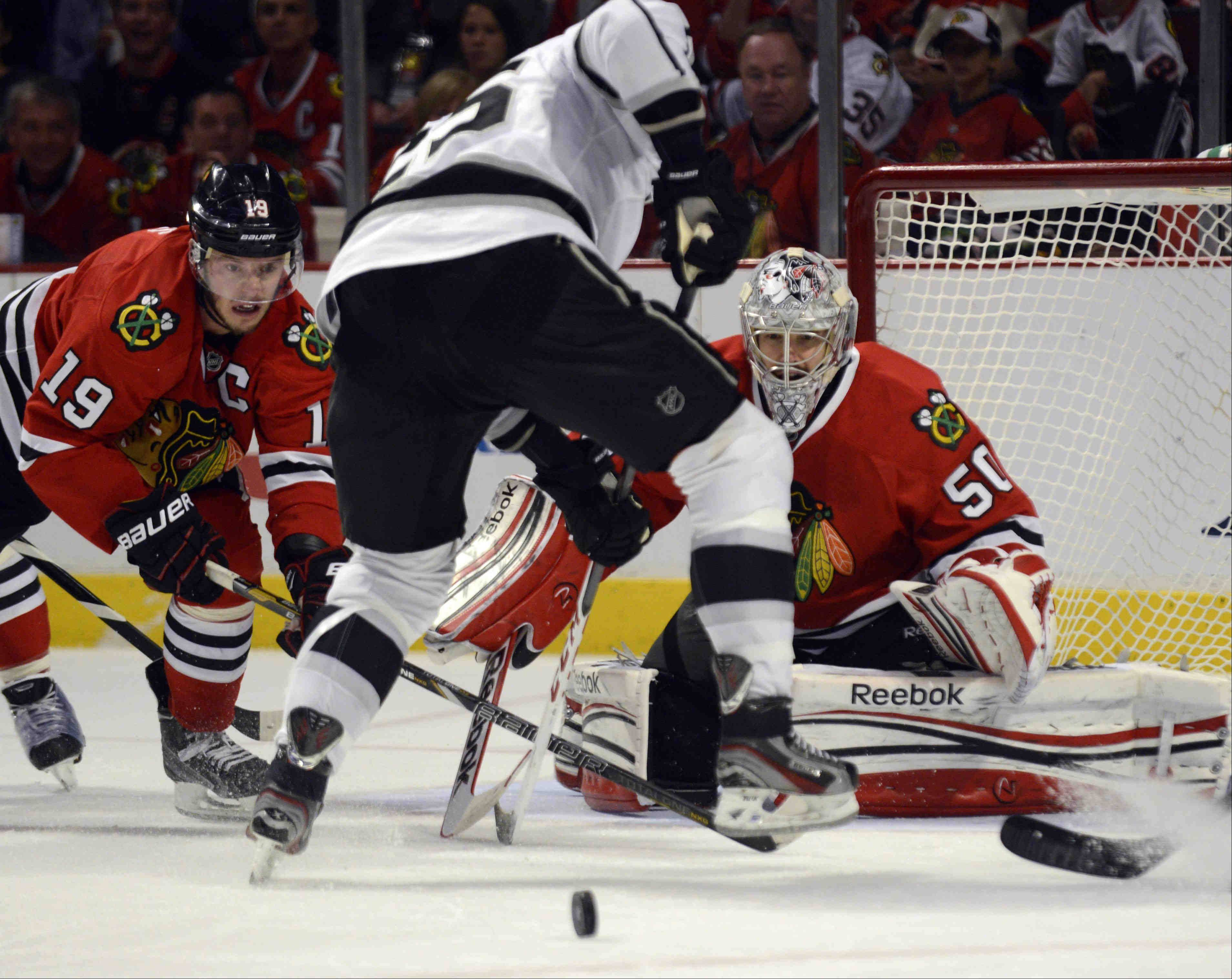 Chicago Blackhawks goalie Corey Crawford and teammate Jonathan Toews watch the puck roll away from Los Angeles Kings left wing Dustin Penner in the second period as he charged the net during Game 2 of the NHL Western Conference finals at the United Center Sunday night in Chicago.