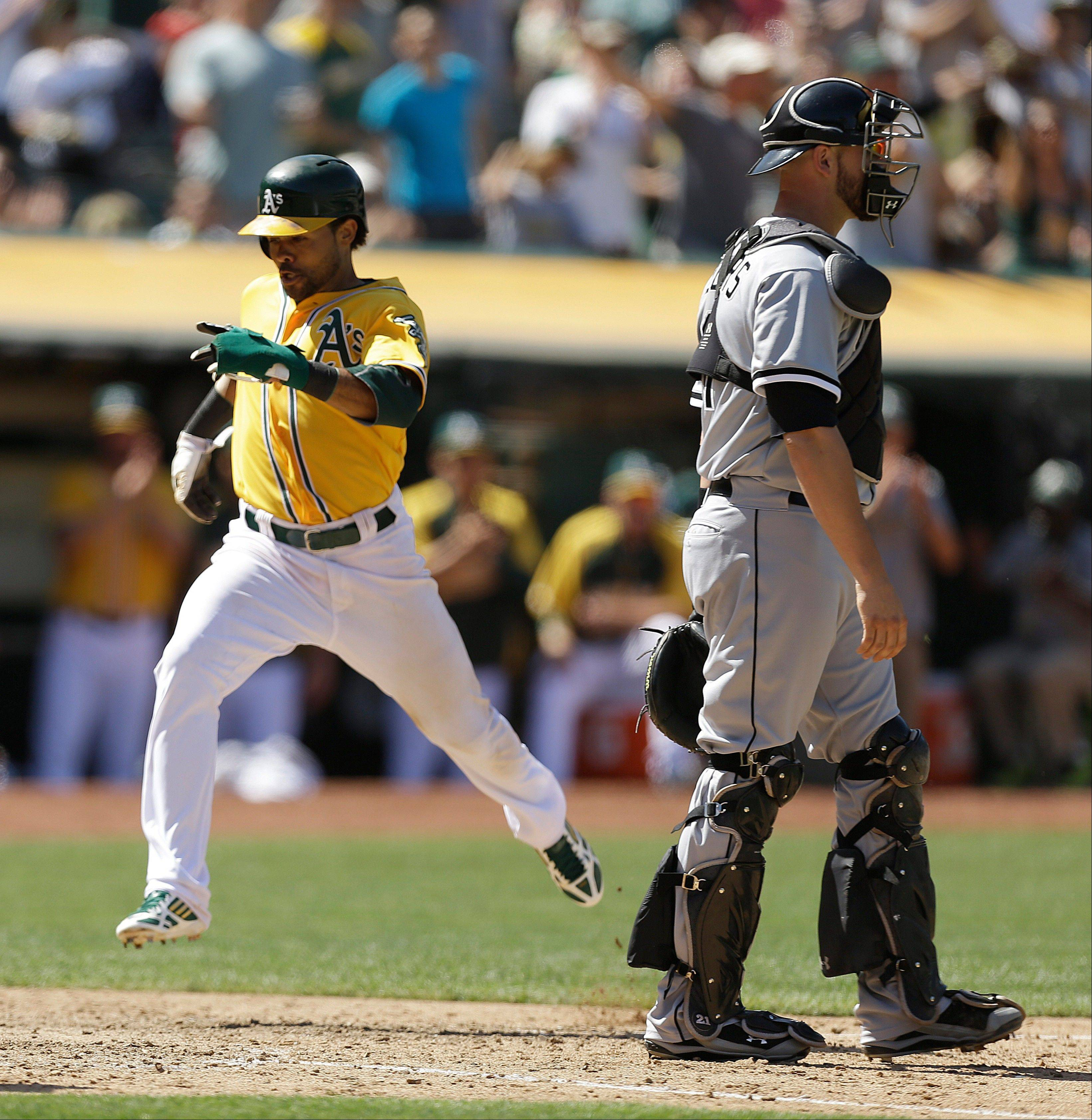 Oakland Athletics' Coco Crisp, left, scores past Chicago White Sox catcher Tyler Flowers in the eighth inning of a baseball game, Sunday, June 2, 2013, in Oakland, Calif. Crisp scored on a single by A's Jed Lowrie.
