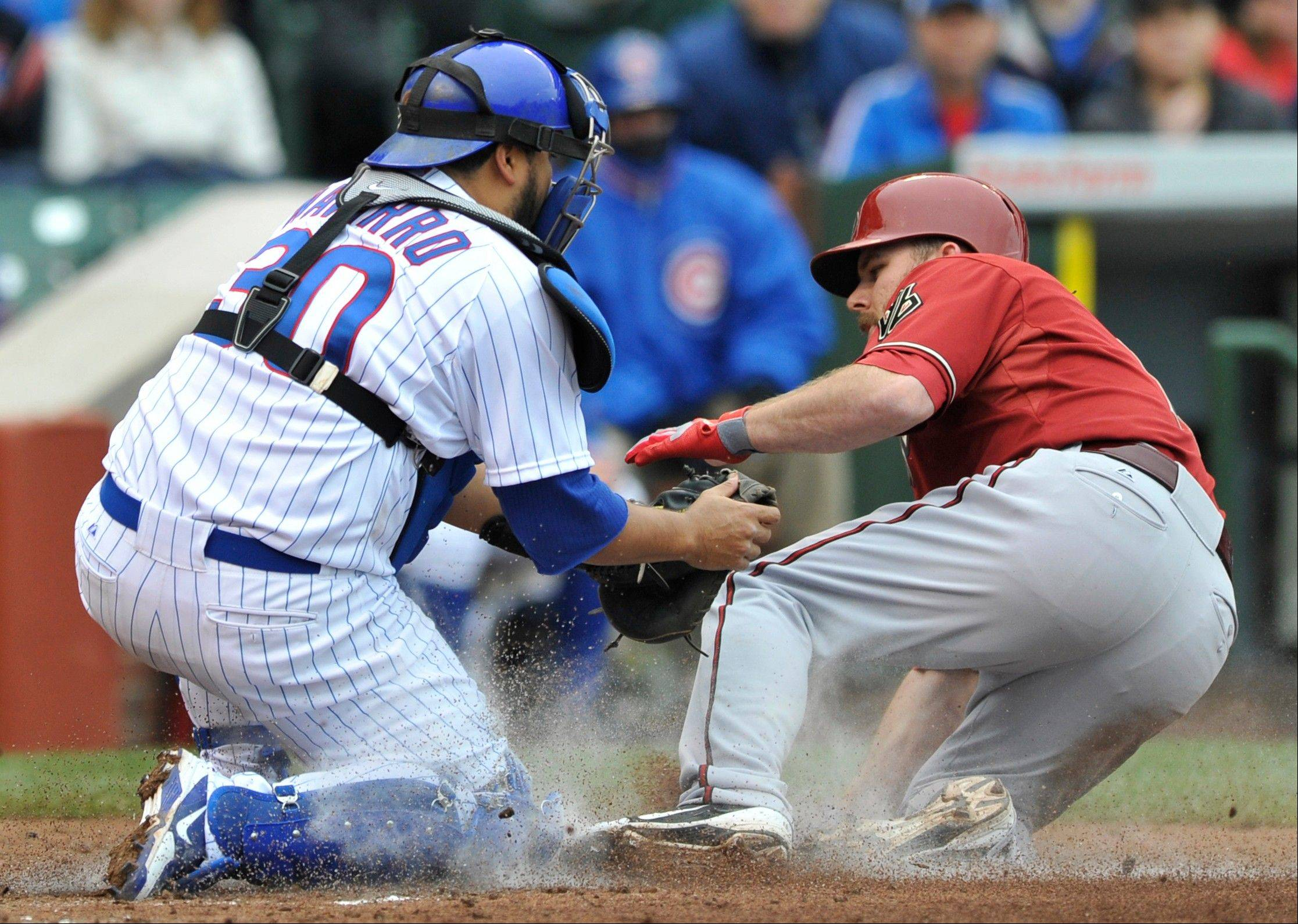 Arizona Diamondbacks' Jason Kubel right is tagged out by Chicago Cubs catcher Dioner Navarro left, at home plate after Wil Nieves grounded into a fielder's choice during the second inning of an MLB baseball game against the Chicago Cubs in Chicago, Sunday, June 2, 2013.