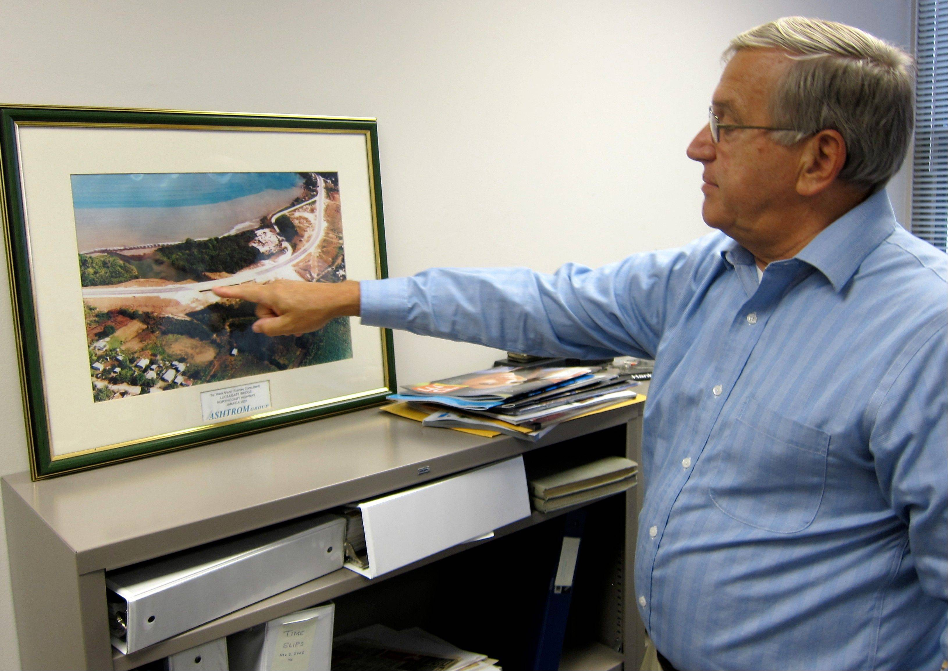 Hank Mann, 72, an engineer at Stanley Consultants, pointing at an image of a highway project he worked on, at the company's headquarters in Muscatine, Iowa.