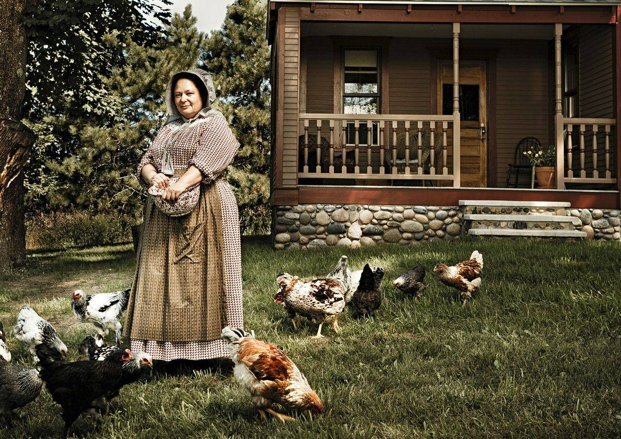 Susan Odom, shown outside her farmhouse feeding the chickens, maintains the year 1910 at her Hillside Homestead Bed & Breakfast in Suttons Bay, Mich.