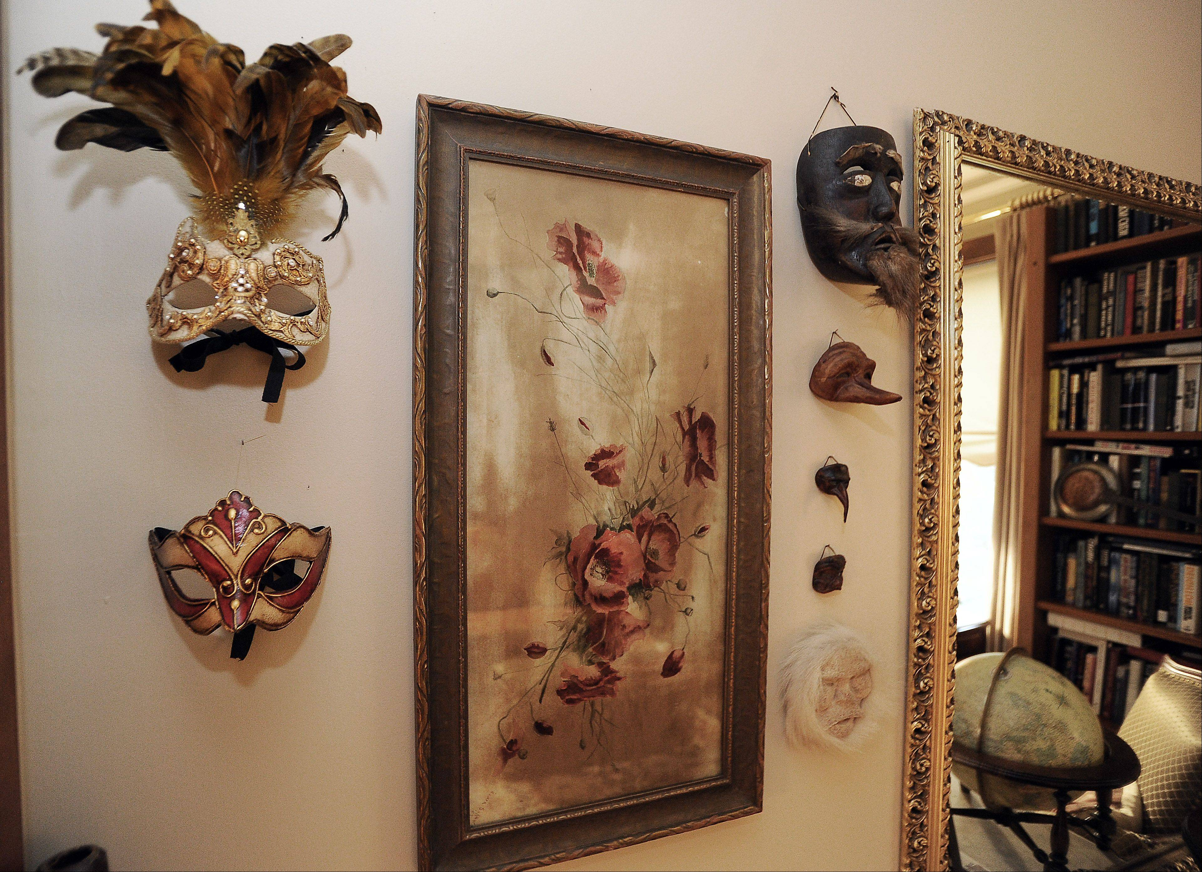 Copies of Venetian masks collected by Laurie Turpin-Soderholm hang on a wall in the library.