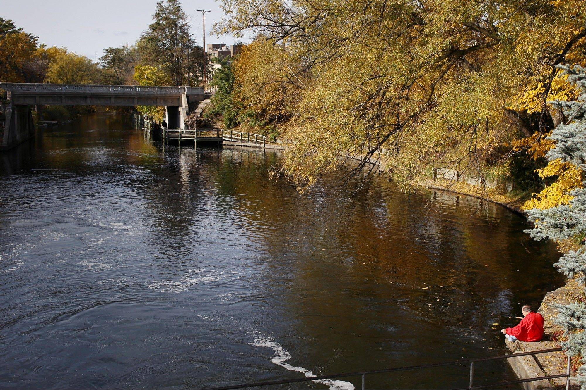 A fisherman sits near the Boardman River dam in Traverse City, Mich. The Boardman River, which meanders through town before flowing into the lake.