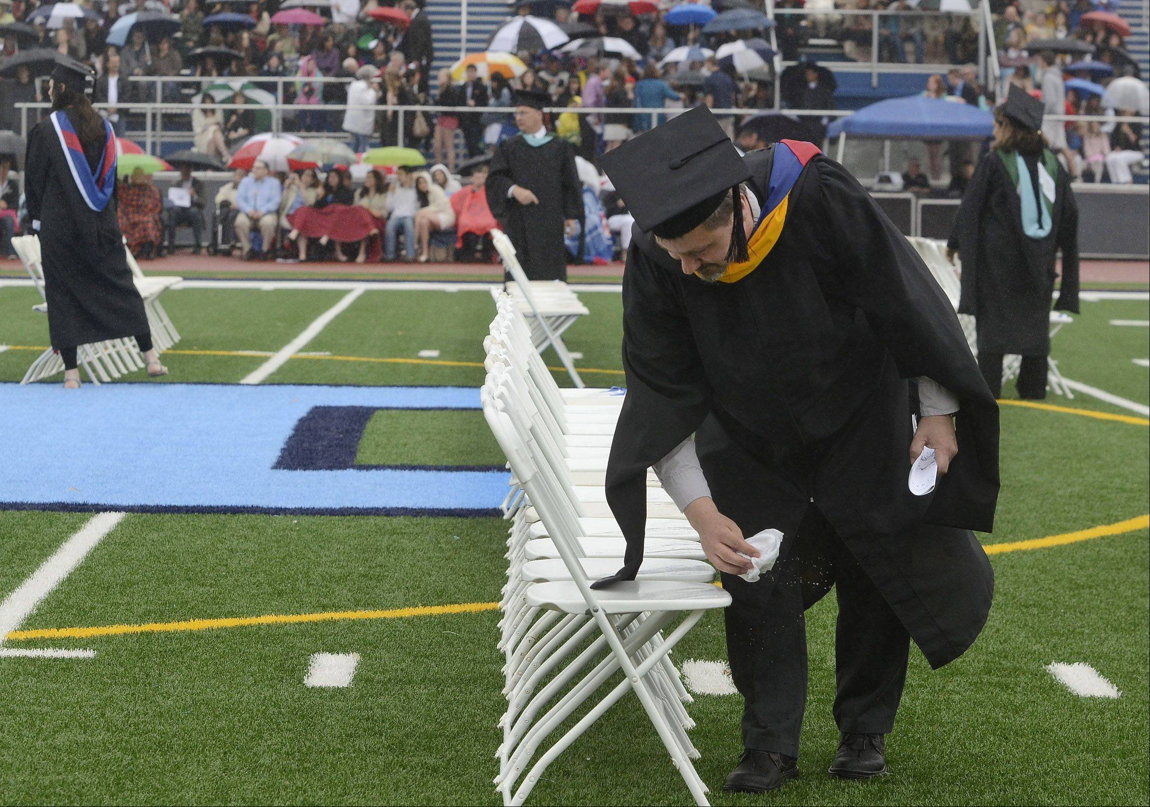 Math teacher Michael Grasse wipes down the seats with other teachers just before the graduates enter the wet football stadium during a damp Prospect High School graduation.