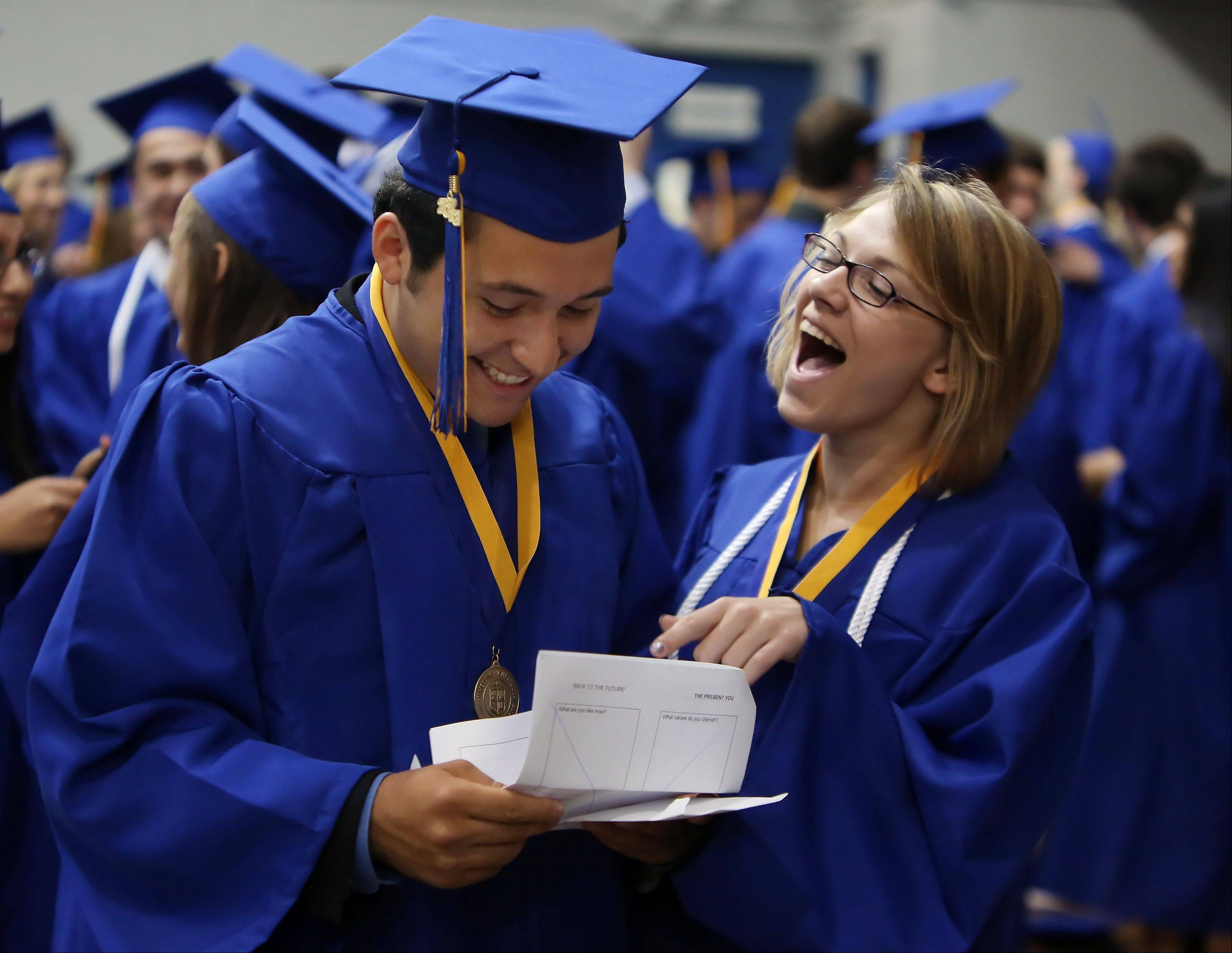 Senior Alfonso Figueroa reads a letter with Kaitlyn Nielsen that he wrote as a freshman stating his goals and reflecting on his future before the Wheeling High School graduation on Sunday, June 2nd, at the school. There were 425 graduating seniors who participated in commencement exercises