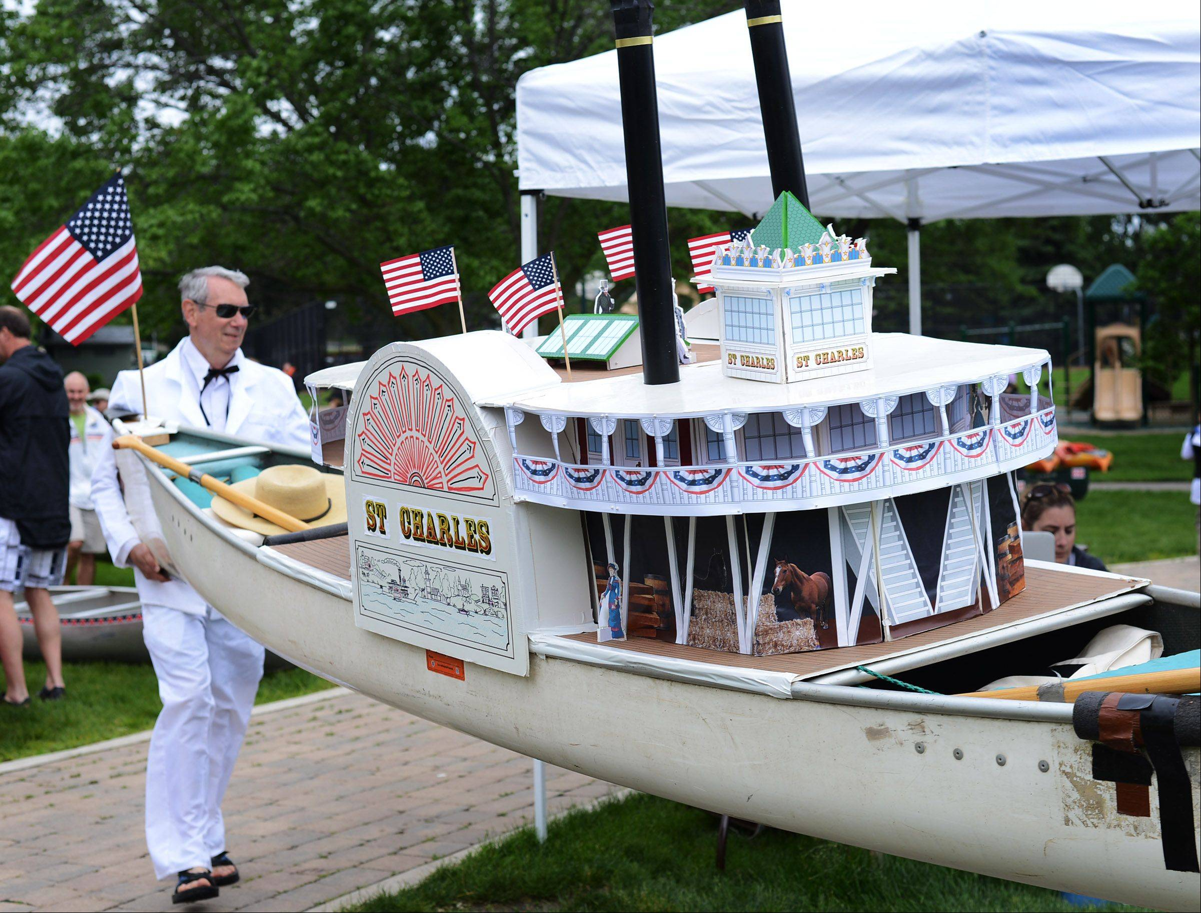 Dressed as Mark Twain, Martin Cassell launches his canoe into the Fox River in St. Charles on Sunday for the 52nd Mid-American Canoe and Kayak Race. He and his son have been paddling together for 29 years.