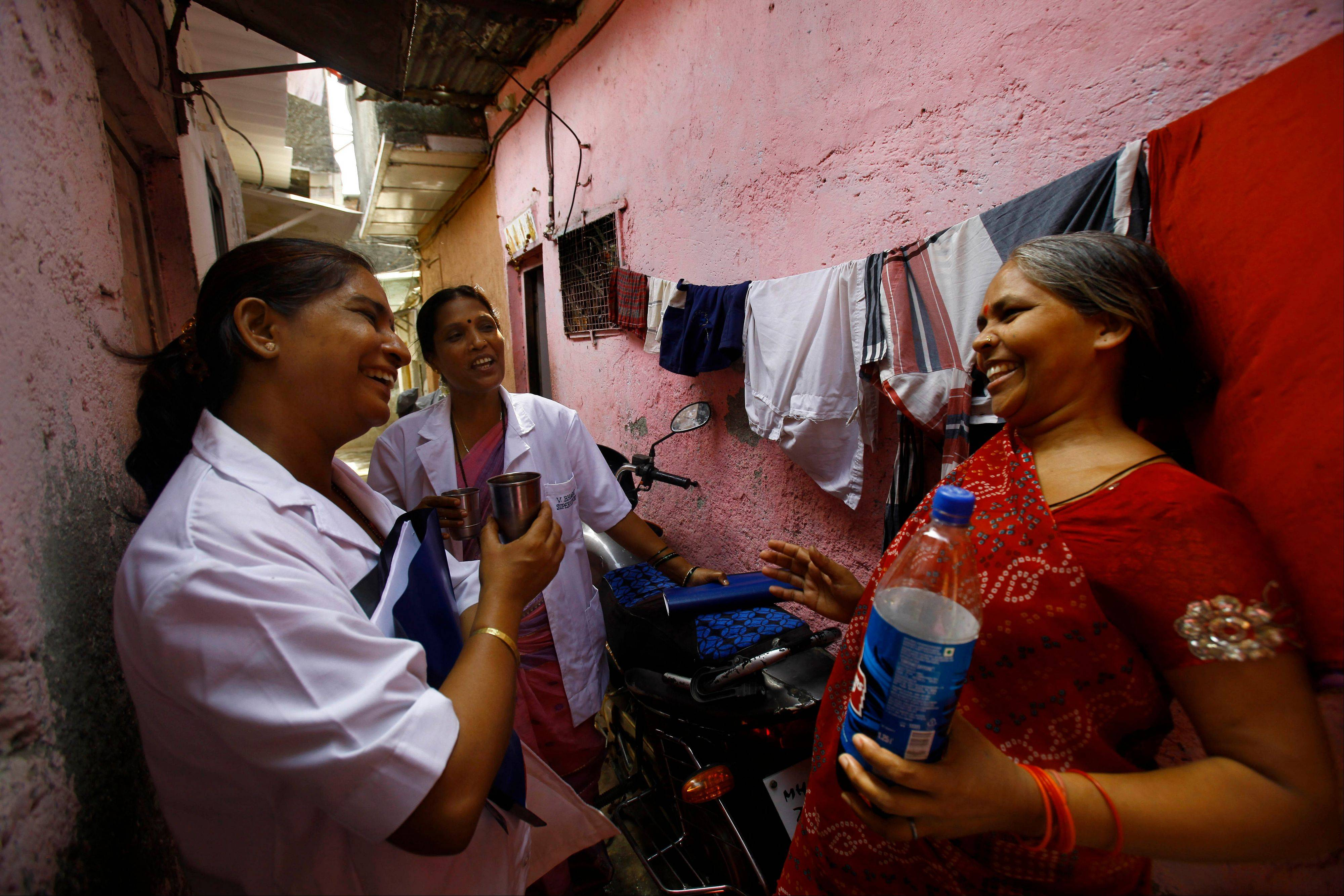 Usha Devi, right, who was suffering from cervical cancer, talks with health workers from Tata Memorial Hospital in a slum in Mumbai, India. A simple vinegar test slashed cervical cancer death rates by one-third in a remarkable study of 150,000 women in the slums of India, where the disease is the top cancer killer of women.