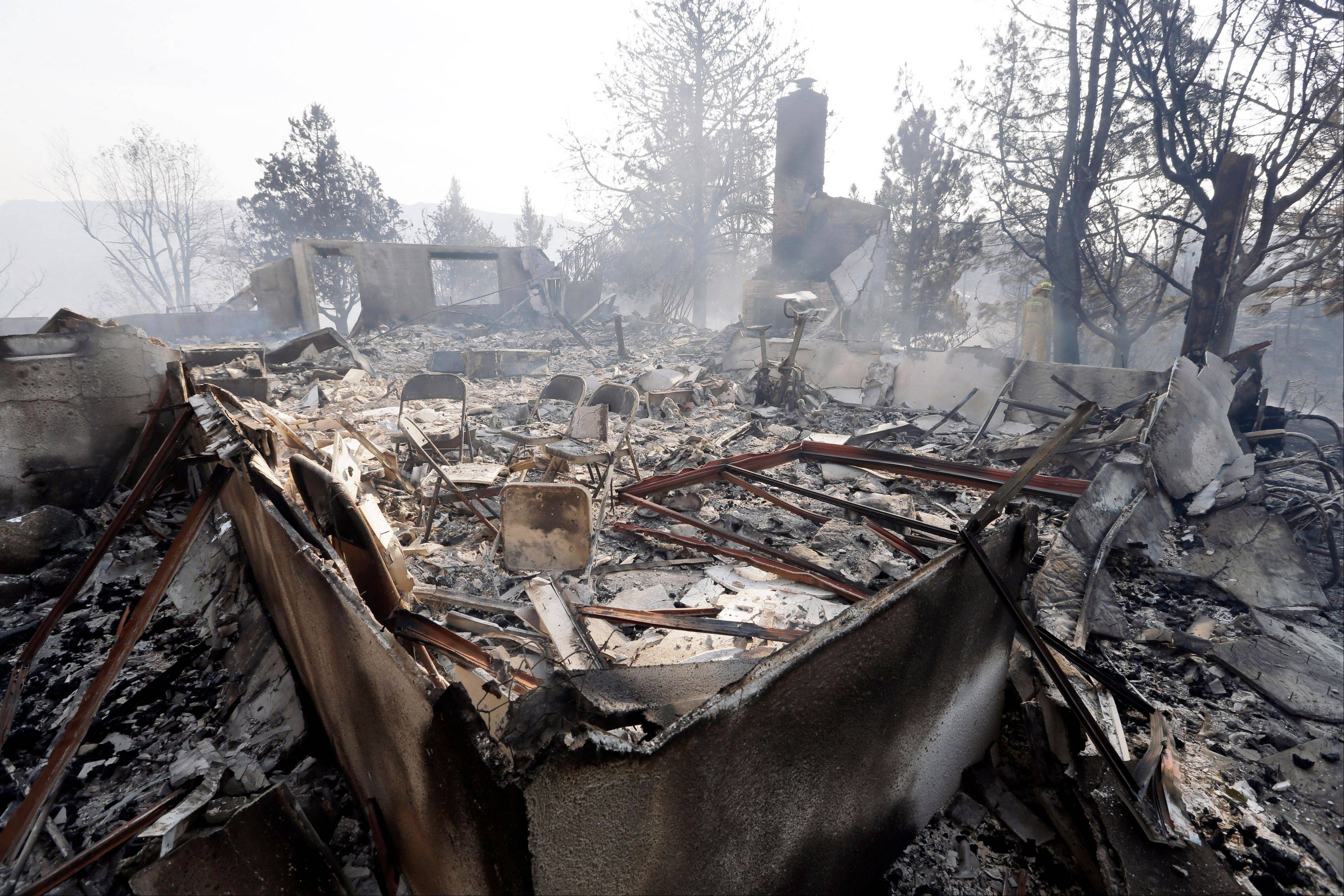 Smoke rises from the remains of a destroyed home in Lake Hughes, Calif., Sunday. Erratic winds fanned a blaze in the Angeles National Forest to nearly 41 square miles early Sunday, after fast-moving flames triggered the evacuation of nearly 1,000 homes in Lake Hughes and Lake Elizabeth, officials said.