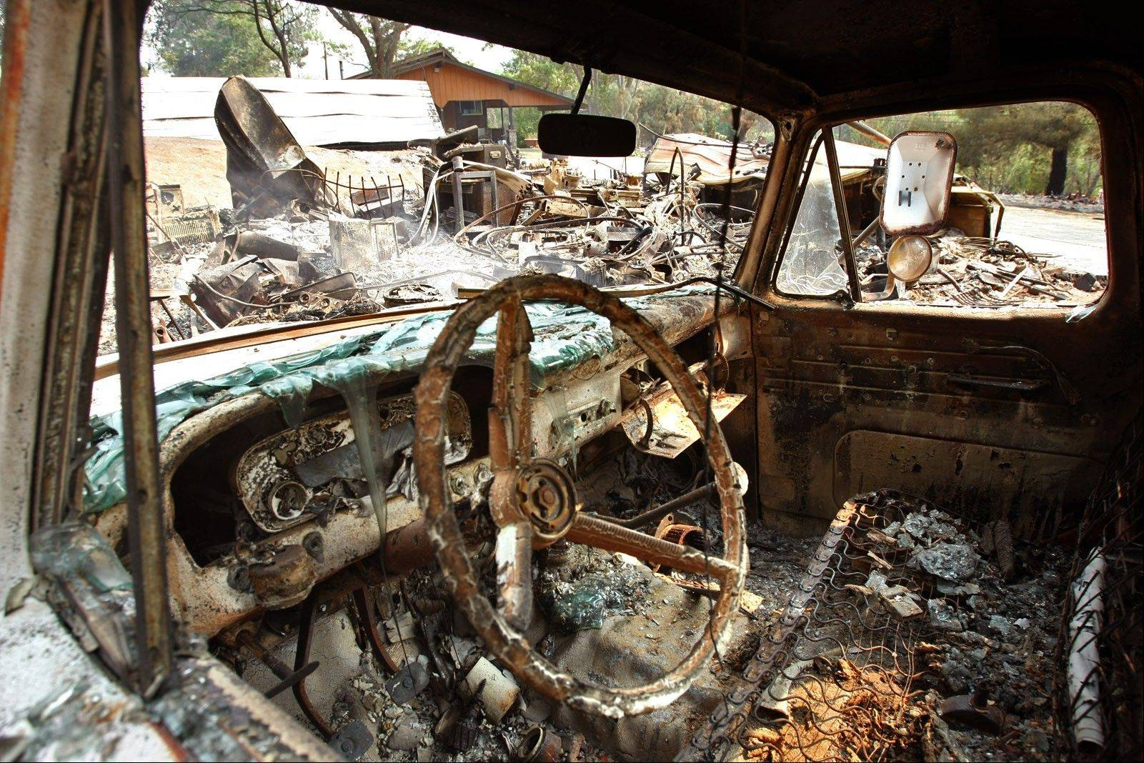 This truck and storage structure were burned by a wildfire in Lake Hughes, Calif., Sunday.