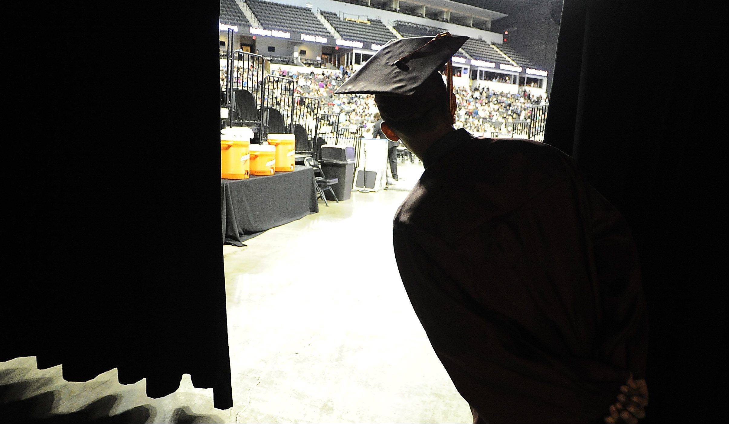 Nathaniel Lozano, 18, of Hanover Park peeks from behind a curtain as he looks at the huge crowd in attendance for the Schaumburg High School forty-first annual commencement at the Sears Centre in Hoffman Estates on Sunday.