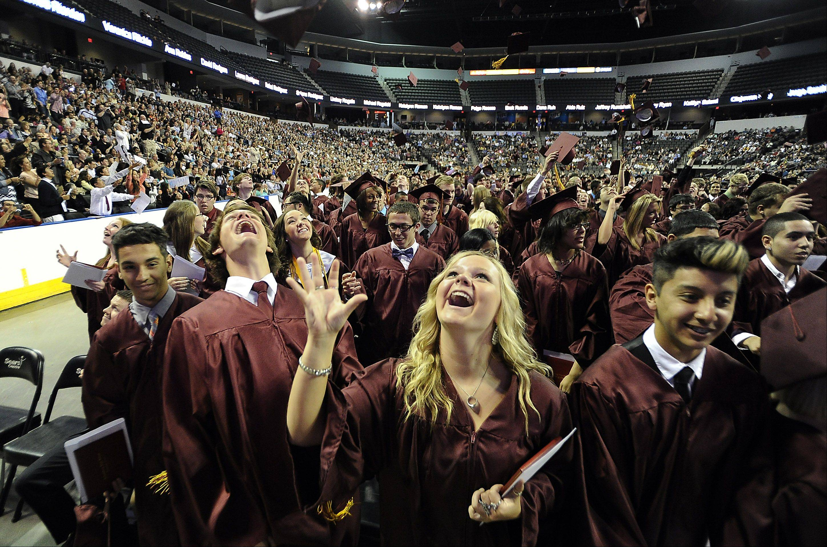 Cameron Mager, 17, and Taisa Madden, 18, both of Schaumburg celebrate their graduation from Schaumburg High School at the Sears Centre in Hoffman Estates on Sunday.