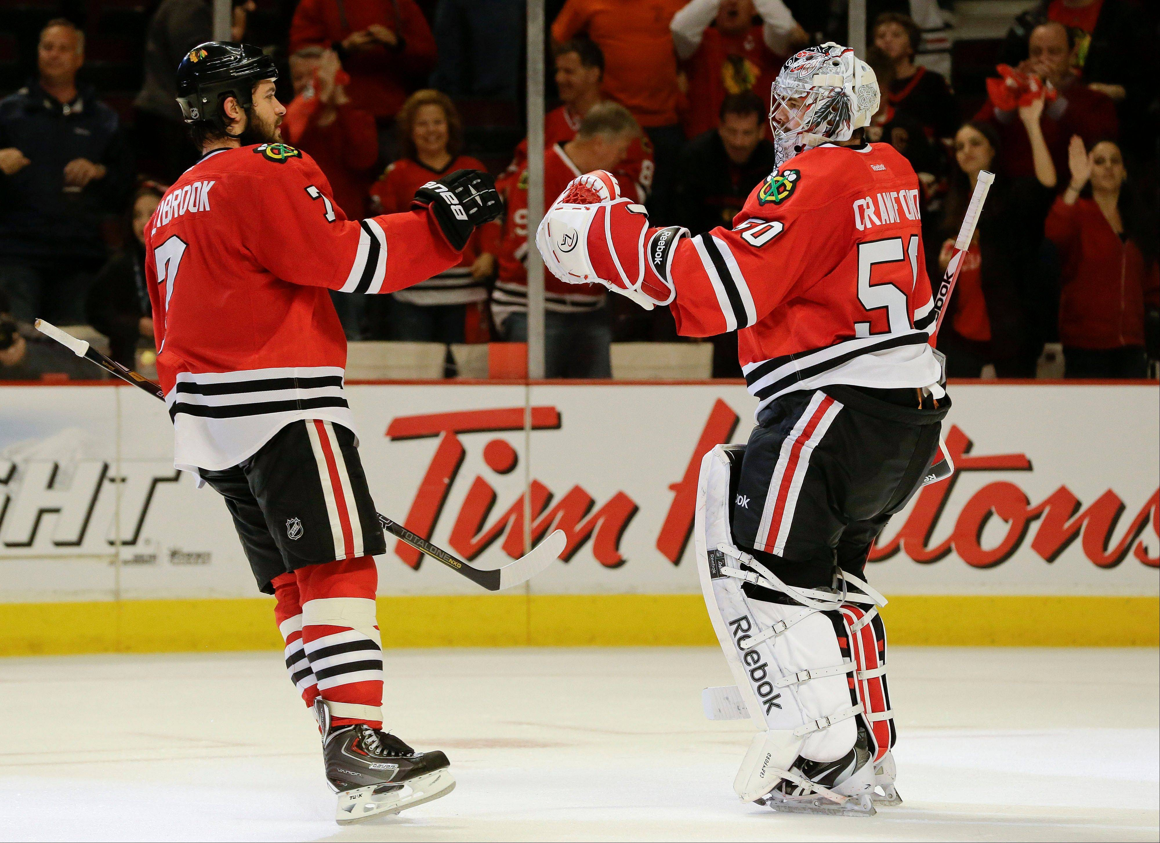 Chicago Blackhawks defenseman Brent Seabrook (7) congratulates goalie Corey Crawford (50) after beating the Los Angeles Kings in Game 2 of an NHL hockey Stanley Cup Western Conference finals, Sunday, June 2, 2013, in Chicago. The Blackhawks won 4-2.