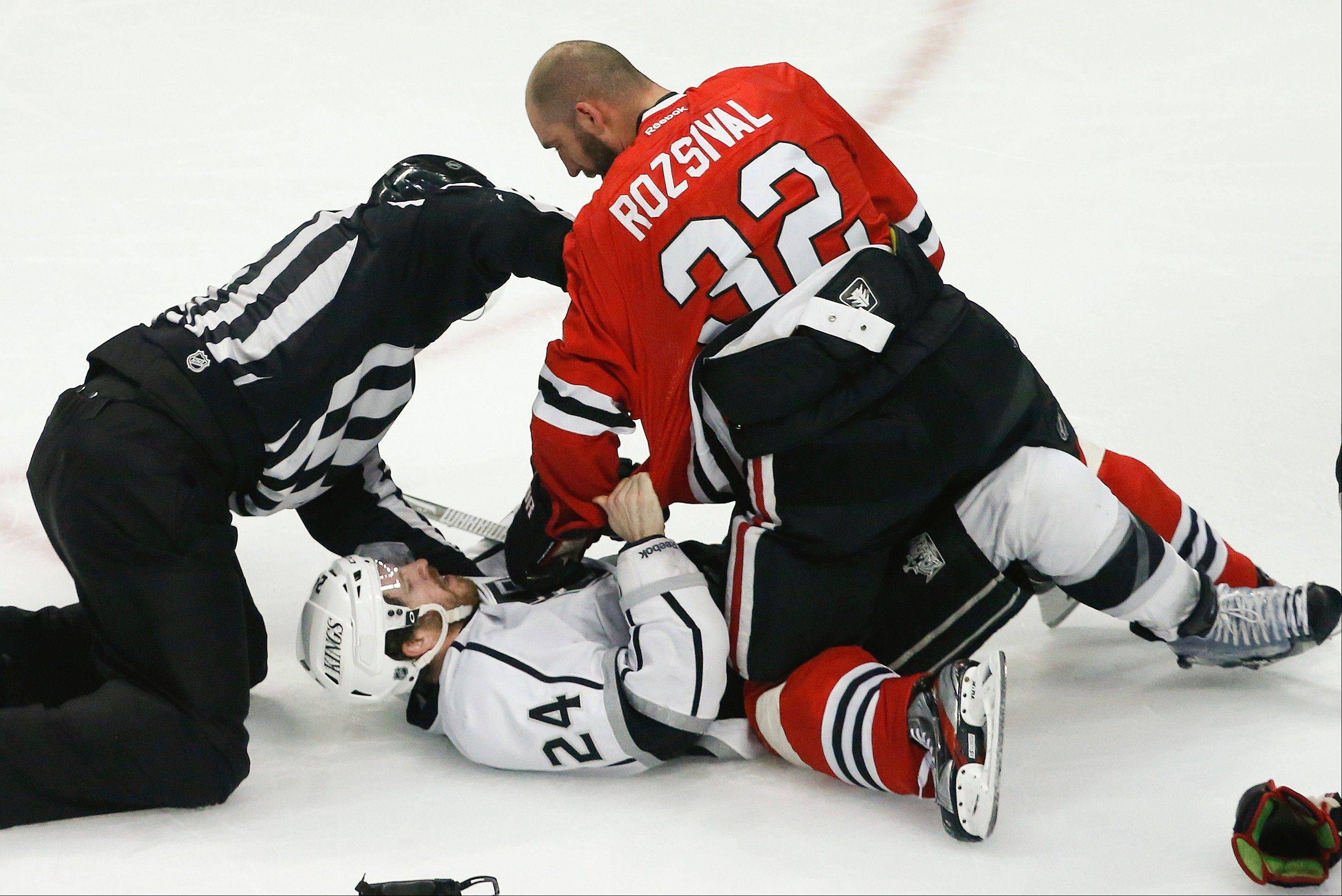 The referee tries to break up a fight between Los Angeles Kings center Colin Fraser (24) and Chicago Blackhawks defenseman Michal Rozsival (32) during the third period in Game 2 of the NHL hockey Stanley Cup Western Conference finals Sunday, June 2, 2013 in Chicago. Chicago won 4-2.