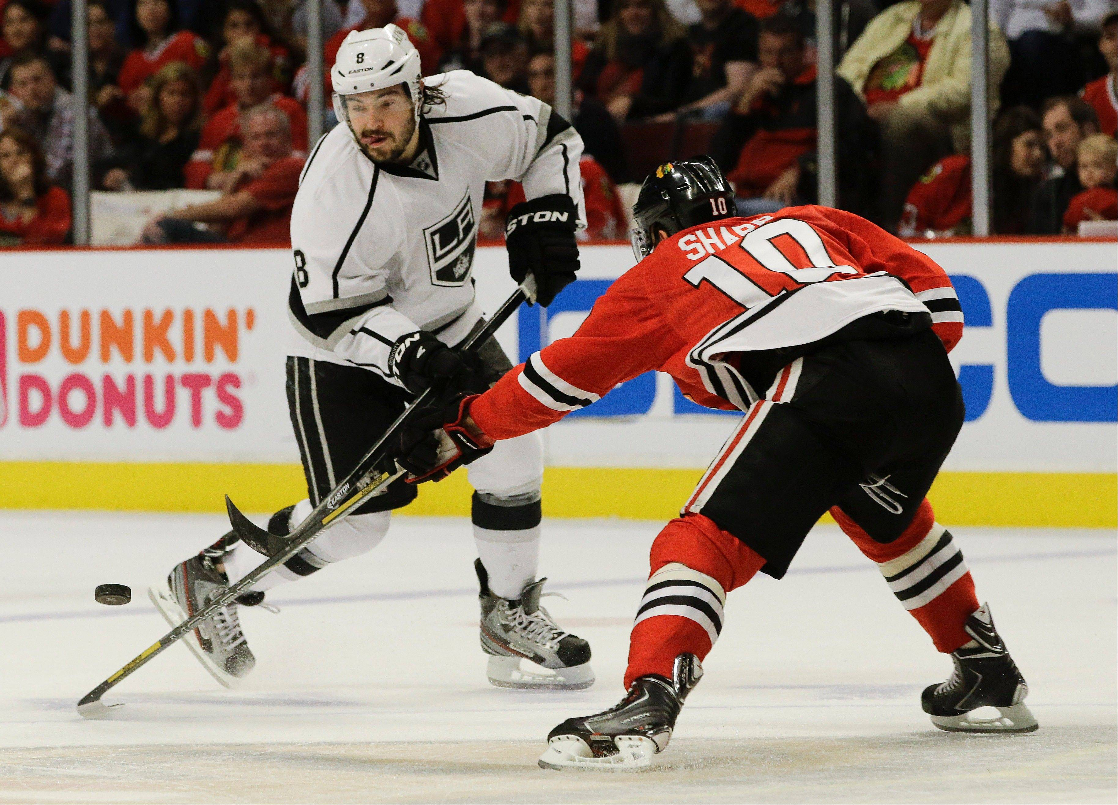 Los Angeles Kings defenseman Drew Doughty (8) battles for the puck against Chicago Blackhawks center Patrick Sharp (10) during the first period of Game 2 of the NHL hockey Stanley Cup Western Conference finals, Sunday, June 2, 2013, in Chicago.