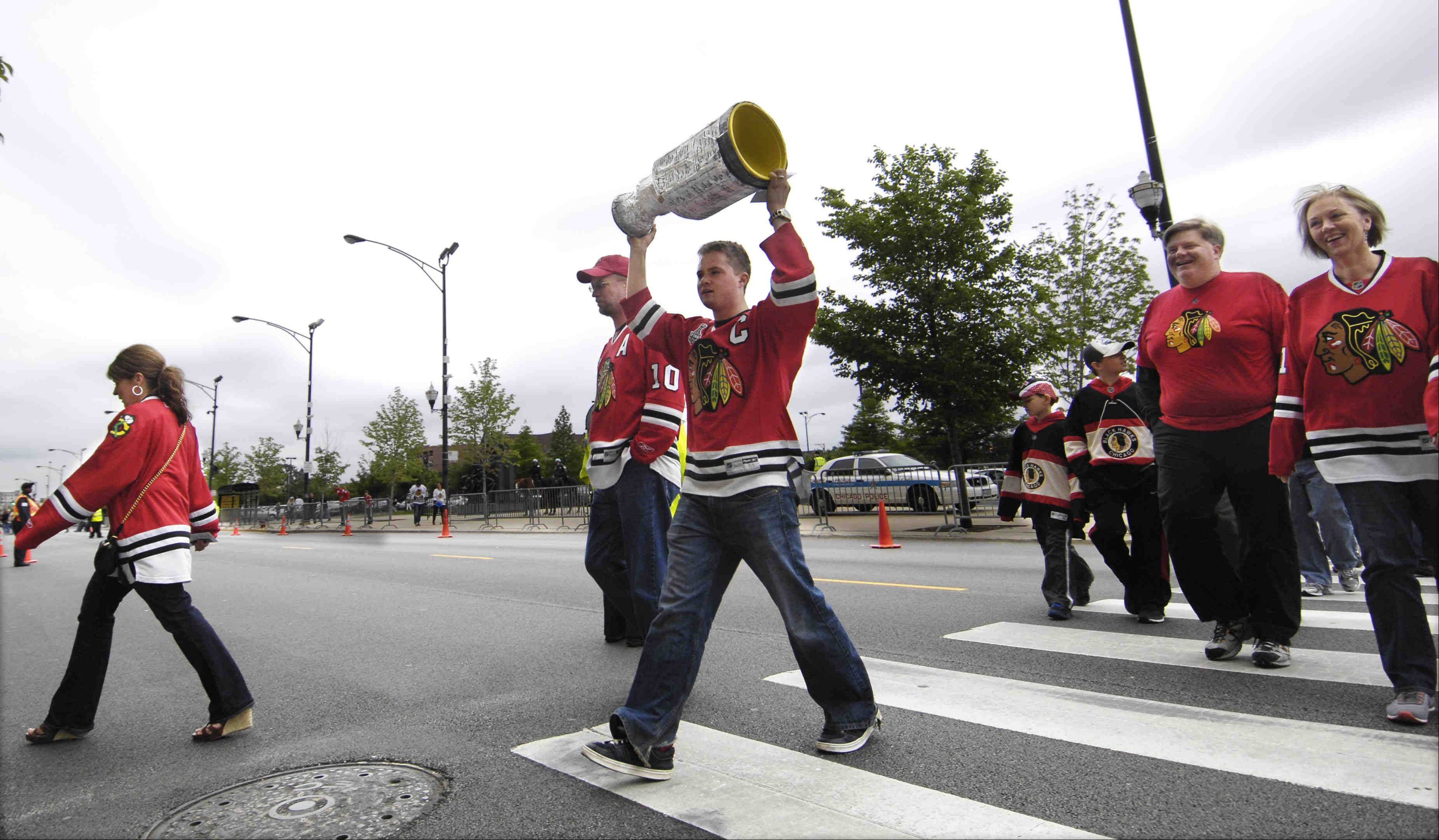 Mike Steele, 19, of Naperville, holds his homemade Stanley Cup aloft as he makes his way across Madison Avenue on his way to game 2 of the NHL Western Conference finals between the Chicago Blackhawks and Los Angeles Kings at the United Center Sunday night in Chicago.