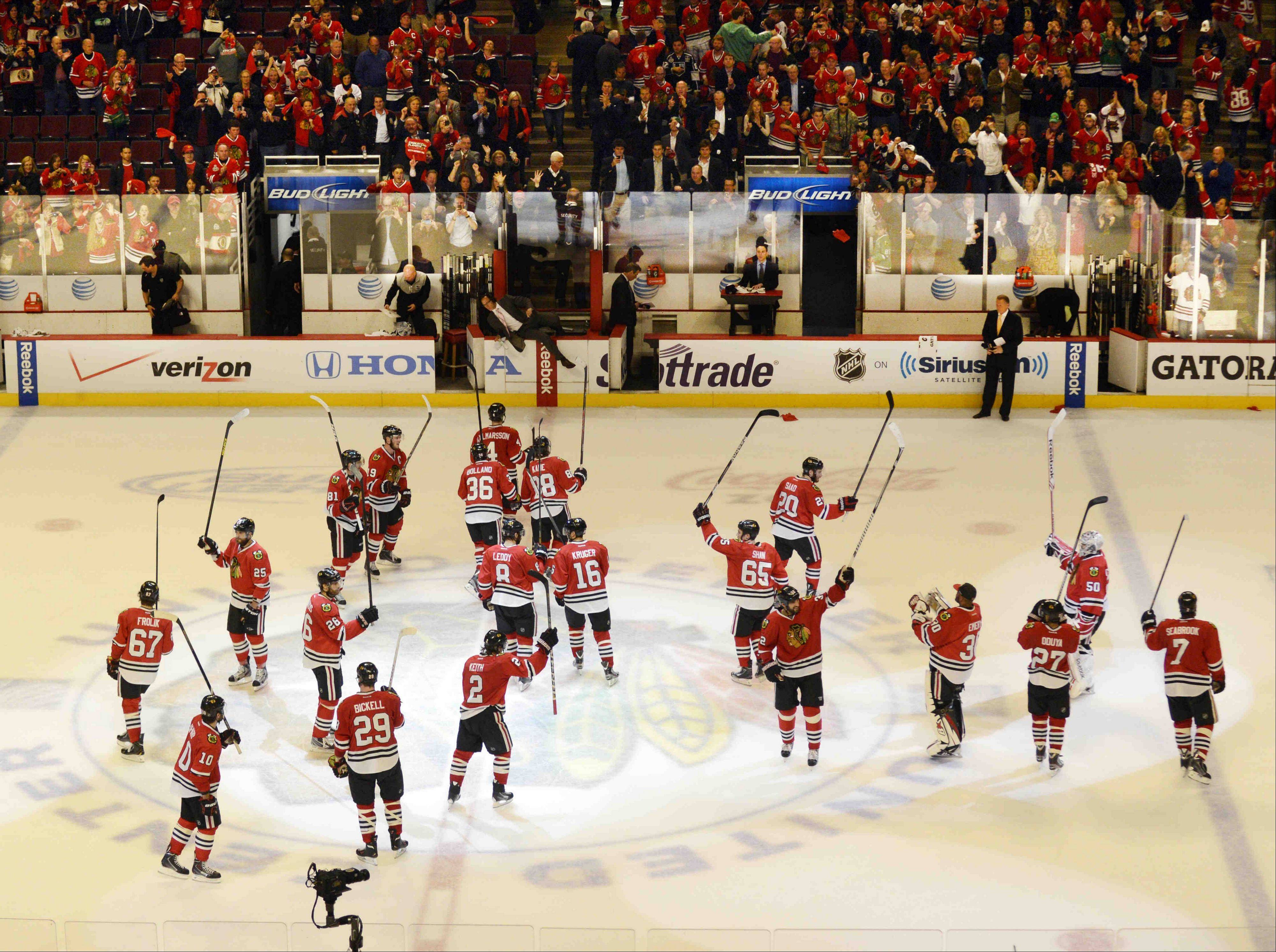 The Chicago Blackhawks raise their sticks in victory after beating the Los Angeles Kings during game 2 of the NHL Western Conference finals at the United Center Sunday night in Chicago.