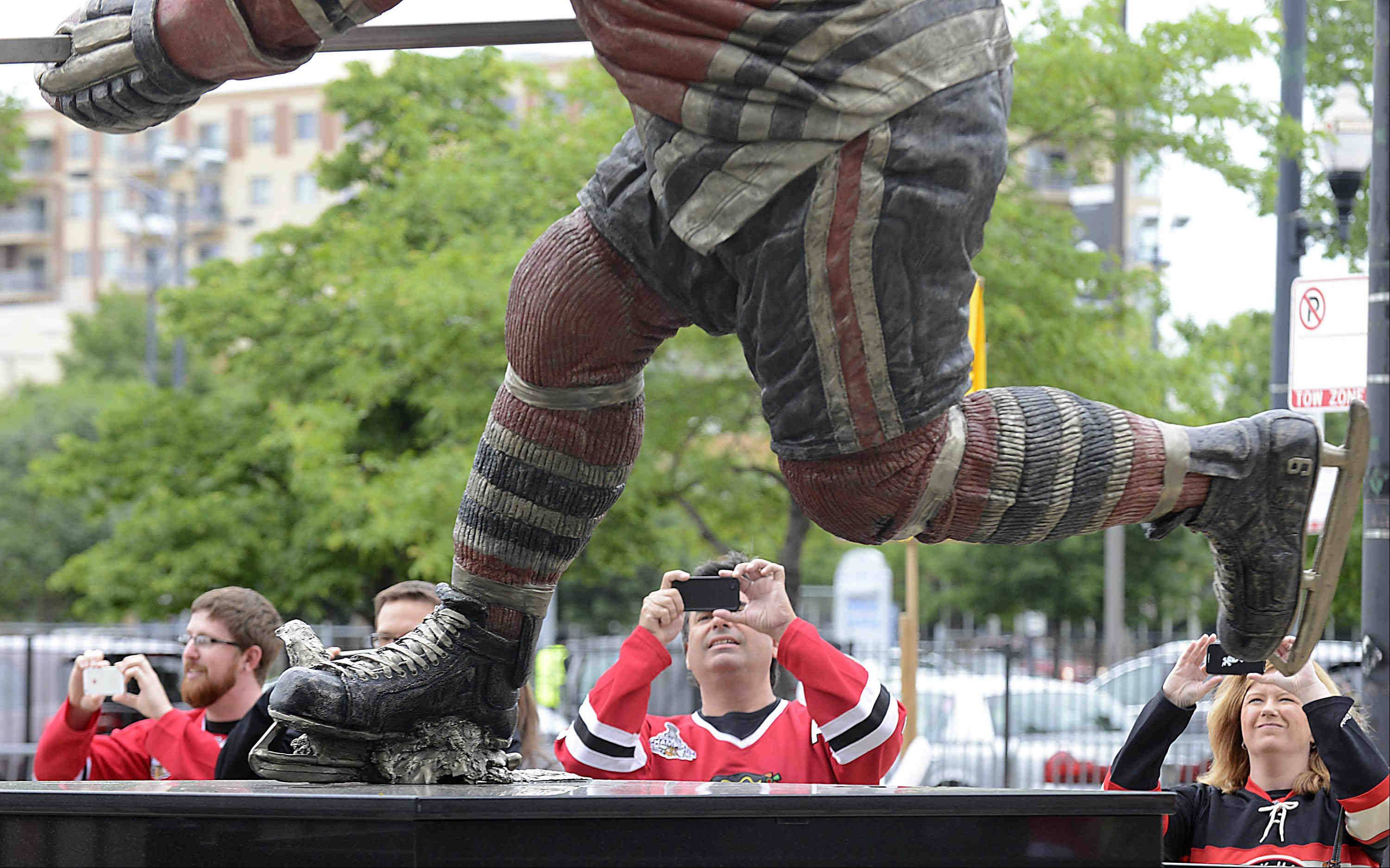 Fans take photos of the Bobby Hull statue before game 2 of the NHL Western Conference finals at the United Center Sunday night in Chicago.