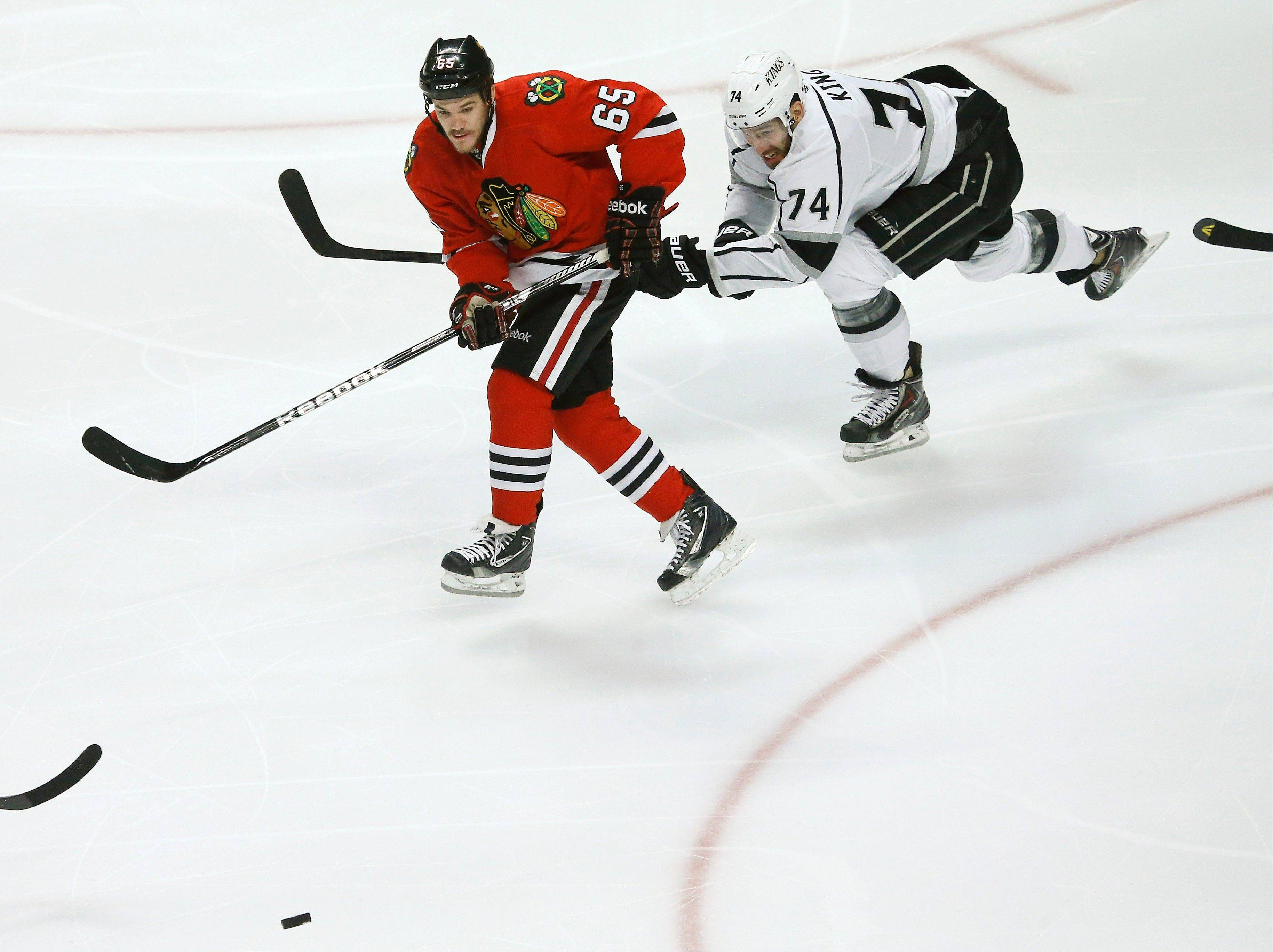 Chicago Blackhawks center Andrew Shaw (65) takes a pass as Los Angeles Kings center Dwight King (74) defends during the first period in Game 2 of the NHL hockey Stanley Cup Western Conference finals Sunday, June 2, 2013 in Chicago. Shaw scored on the play.