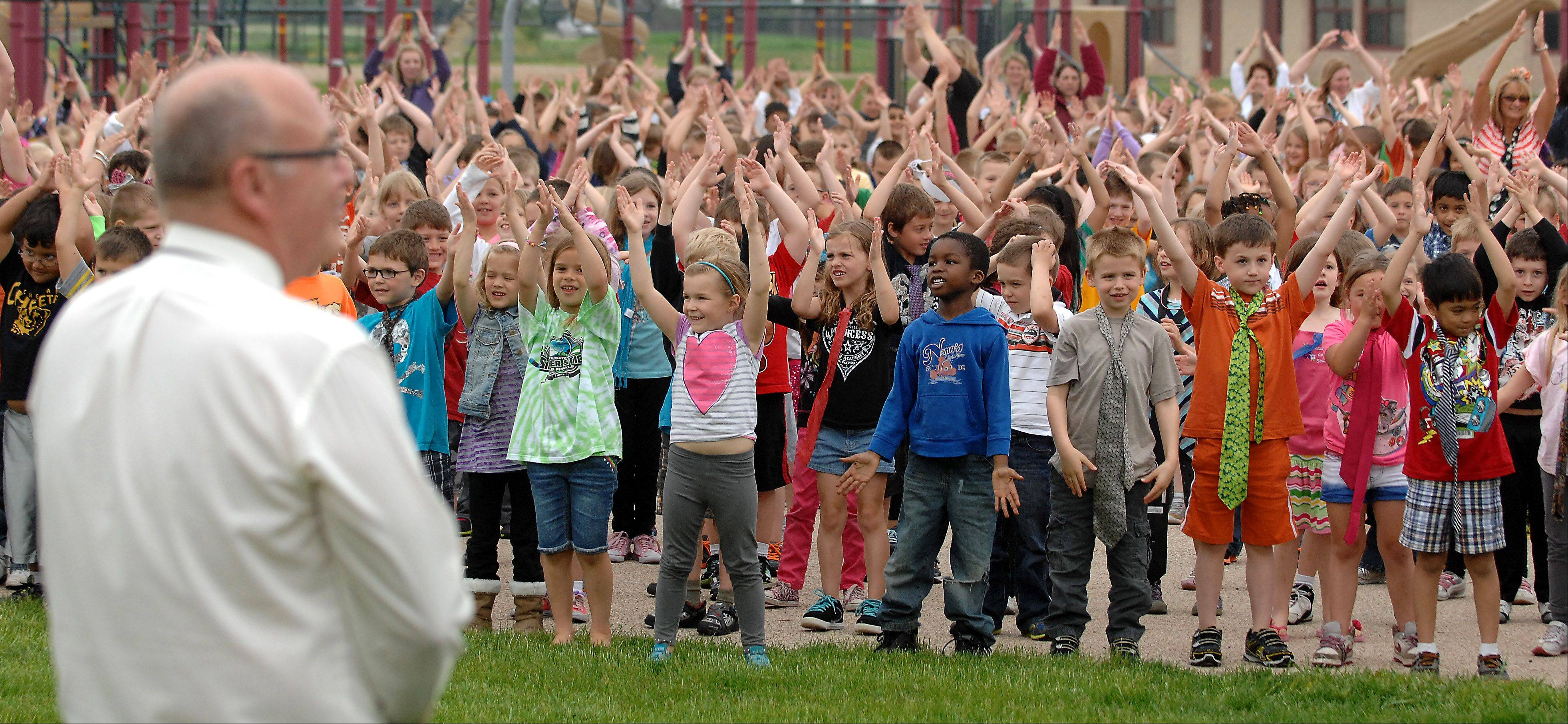 Over 1100 kindergarten, 1st and 2nd-graders perform a surprise song and dance number for retiring principal Chuck Lamb at Chesak Elementary School in Lake in the Hills Tuesday. A whole-school photo had been scheduled and the performace was a surprise that the kids had been working on with their P.E. teachers for the past few weeks.