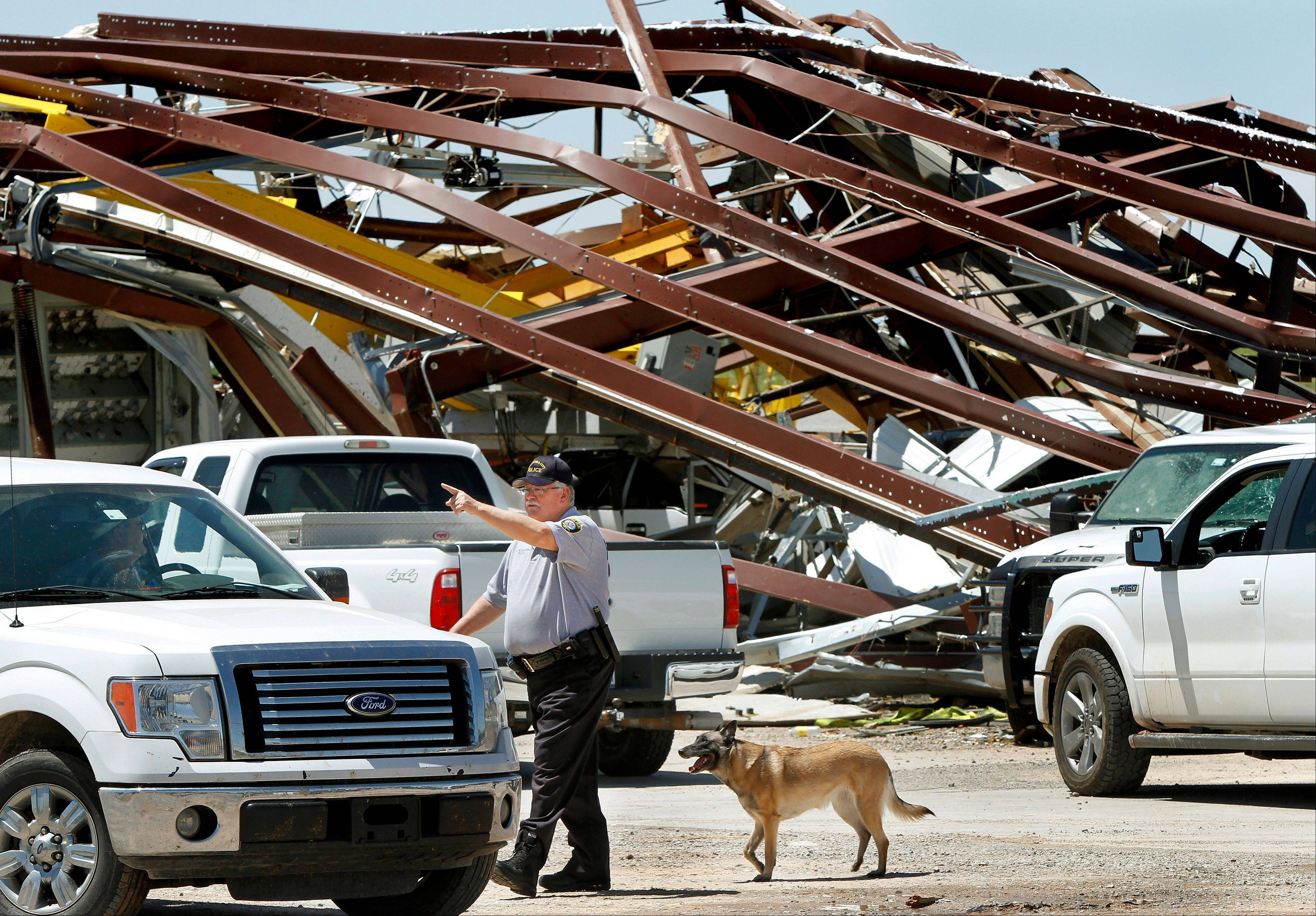 A police officer offers directions to a driver leaving this heavily damaged supply yard for Cactus Drilling Company on State Highway 66 in El Reno, Okla.