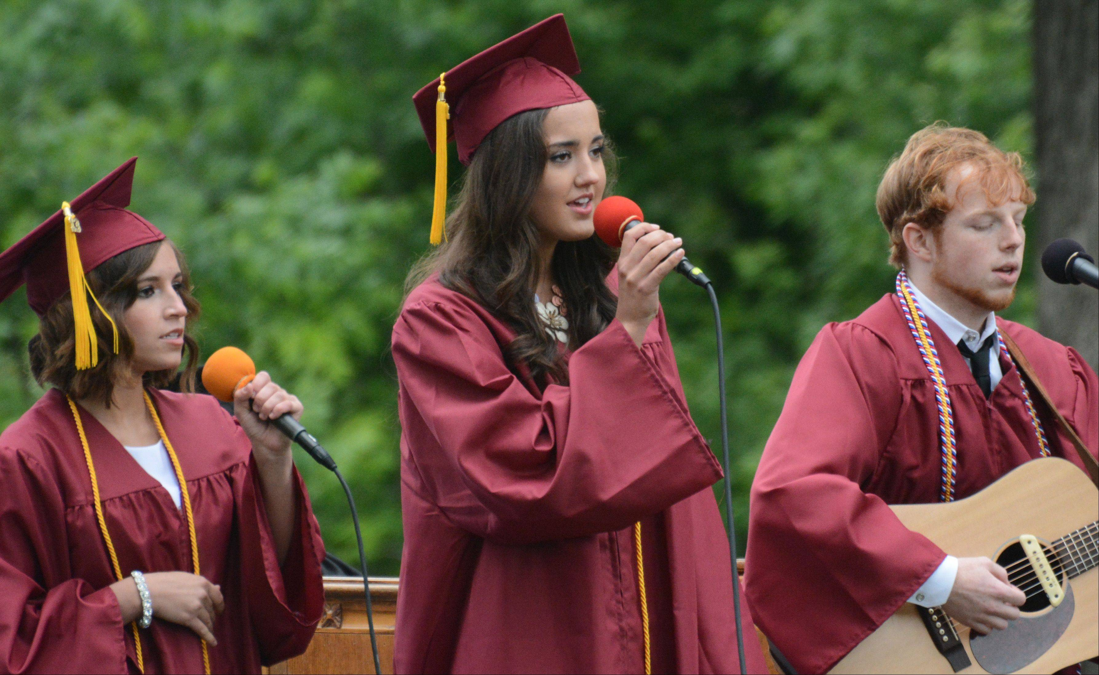 From left, Alexis Shrepple of Carol Stream, Aubrey Martin of Wheaton, and Zachary Naylor of Wheaton perform as a trio at the Wheaton Academy graduation Sunday in West Chicago.