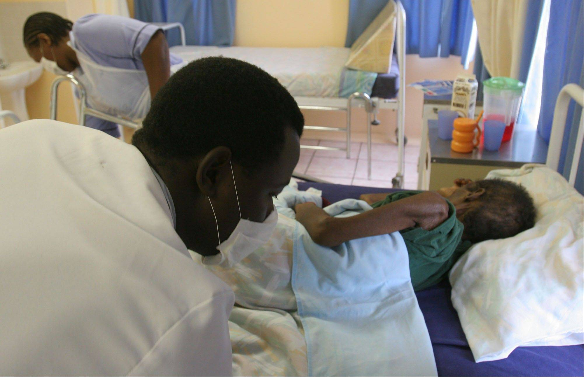 A patient is nursed in the hospice at the AIDS Care Training and Support Initiative at White River Junction, South Africa. The center, partly funded by the President's Emergency Plan for AIDS Relief supports the development of a community-based palliative care unit, which provides care, education and training for staff and community caregivers, volunteer counseling and testing facilities.