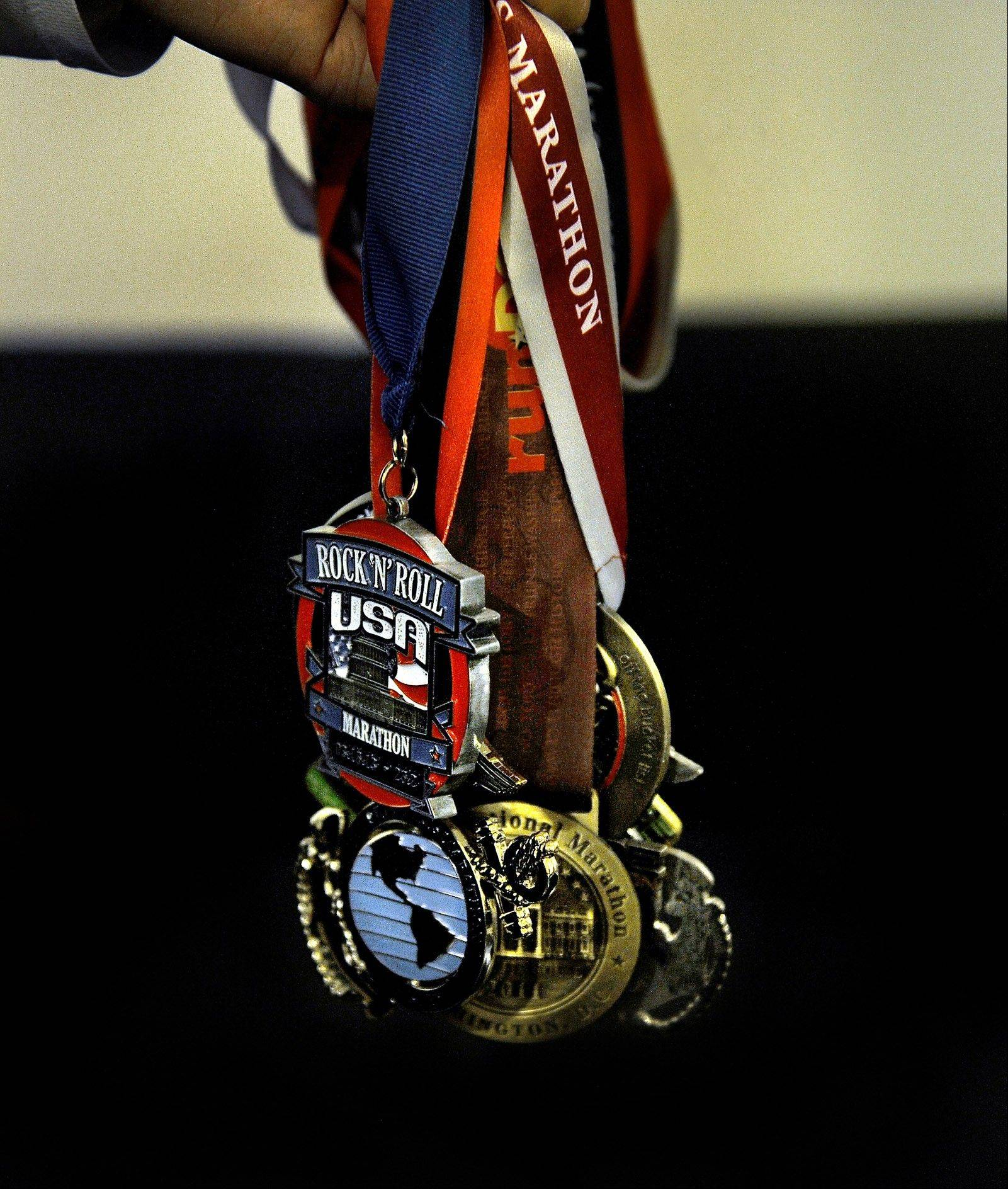 Walter Barrera shows some of the running event medals he's collected from his various long distance competitions.