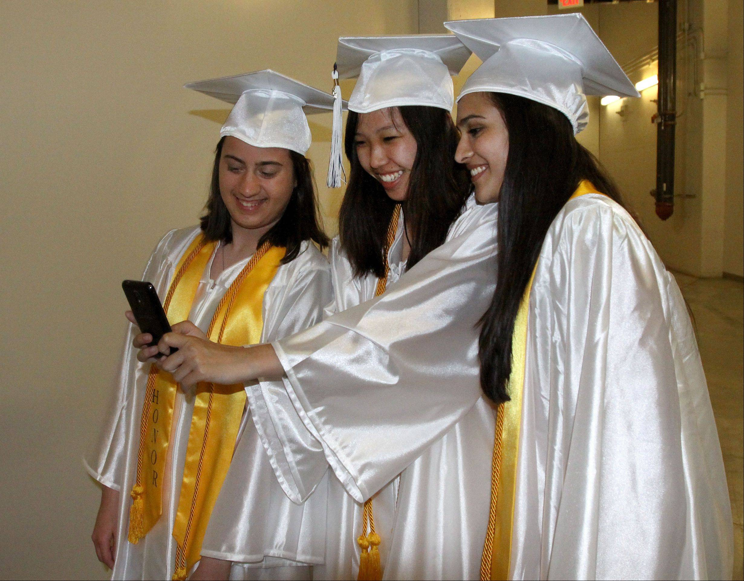 Left to right, Kaitlyn Szabo, Megan McAvoy and Anusha Adkoli get a quick photo before the Lake Park graduation at the Sears Centre in Hoffman Estates on Monday.