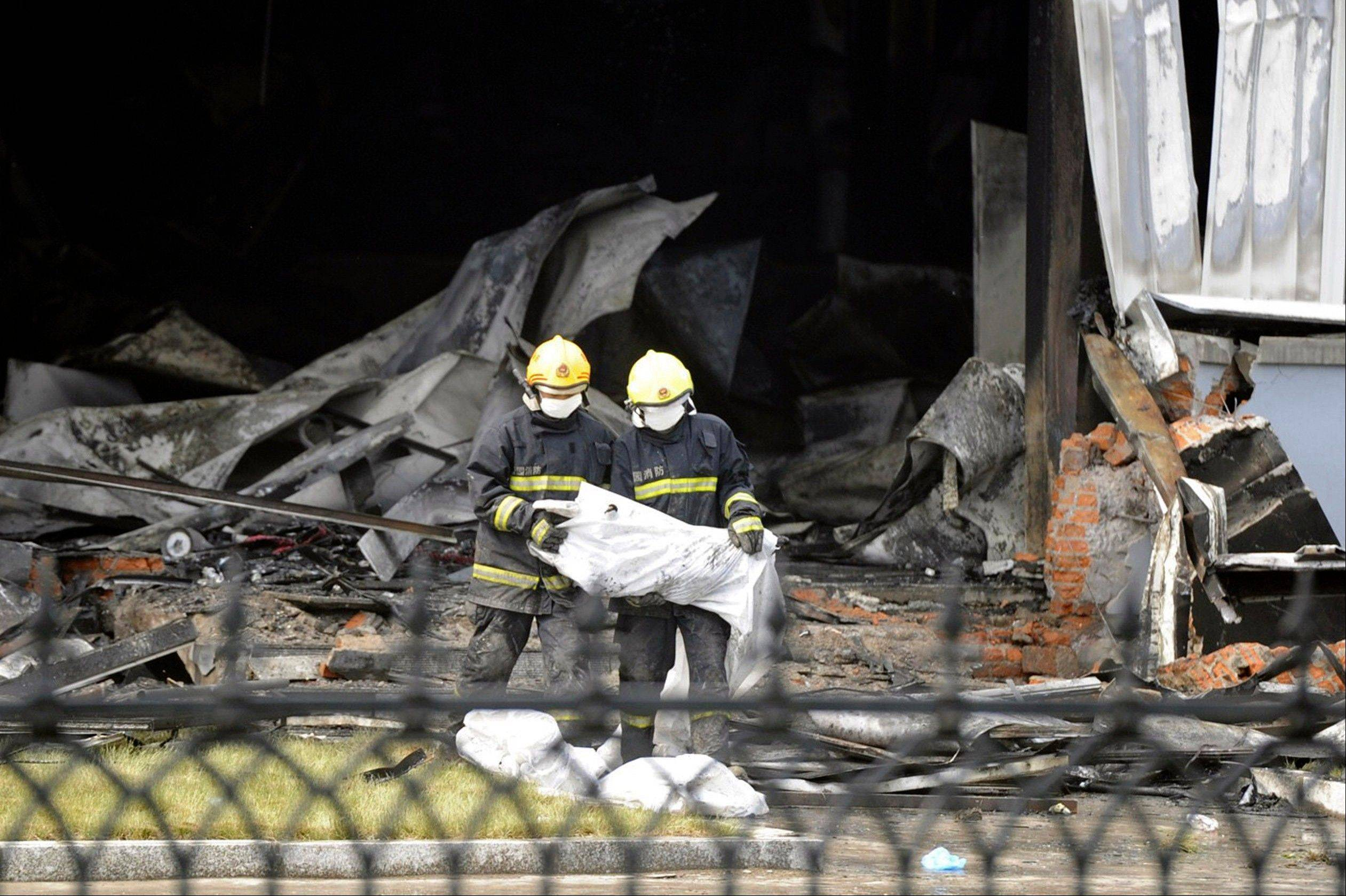 Firefighters prepare bags Monday that appear to contain the remains of victims from a poultry processing plant that was engulfed by a fire in northeast China's Jilin province's Mishazi township. The massive fire broke out here early Monday, trapping workers inside a cluttered slaughterhouse and killing over a hundred people, reports and officials said.