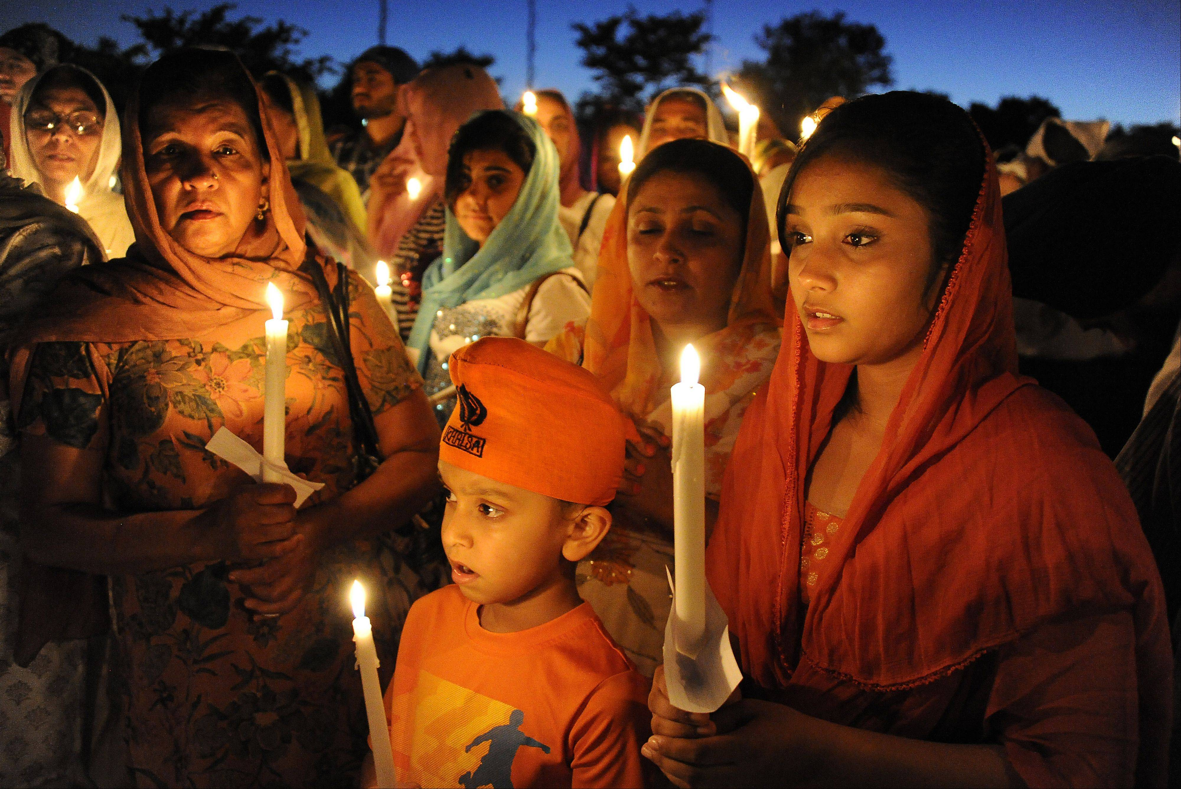 The Sikh Religious Society gurdwara in Palatine held a candlelight vigil with Simmi Dhami, far right, 13, Harsajan Dhami, center, 6, and their mother, Jeewan Dhami, near right, paying their respects to the Sikhs killed in the Wisconsin temple shooting.