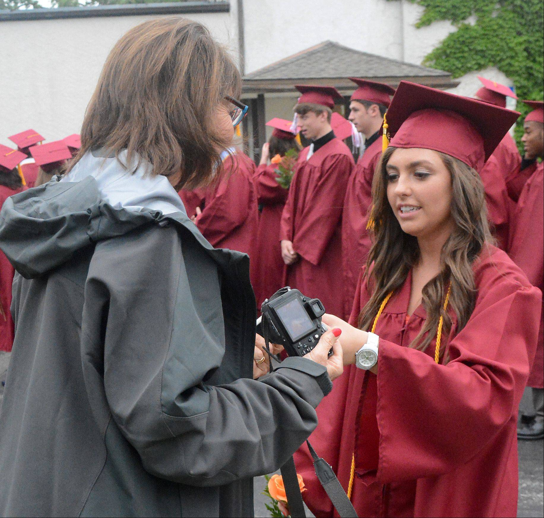 Graduate Caroline Stucki, of Geneva, hands off her phone during the Wheaton Academy Graduation Sunday in West Chicago.