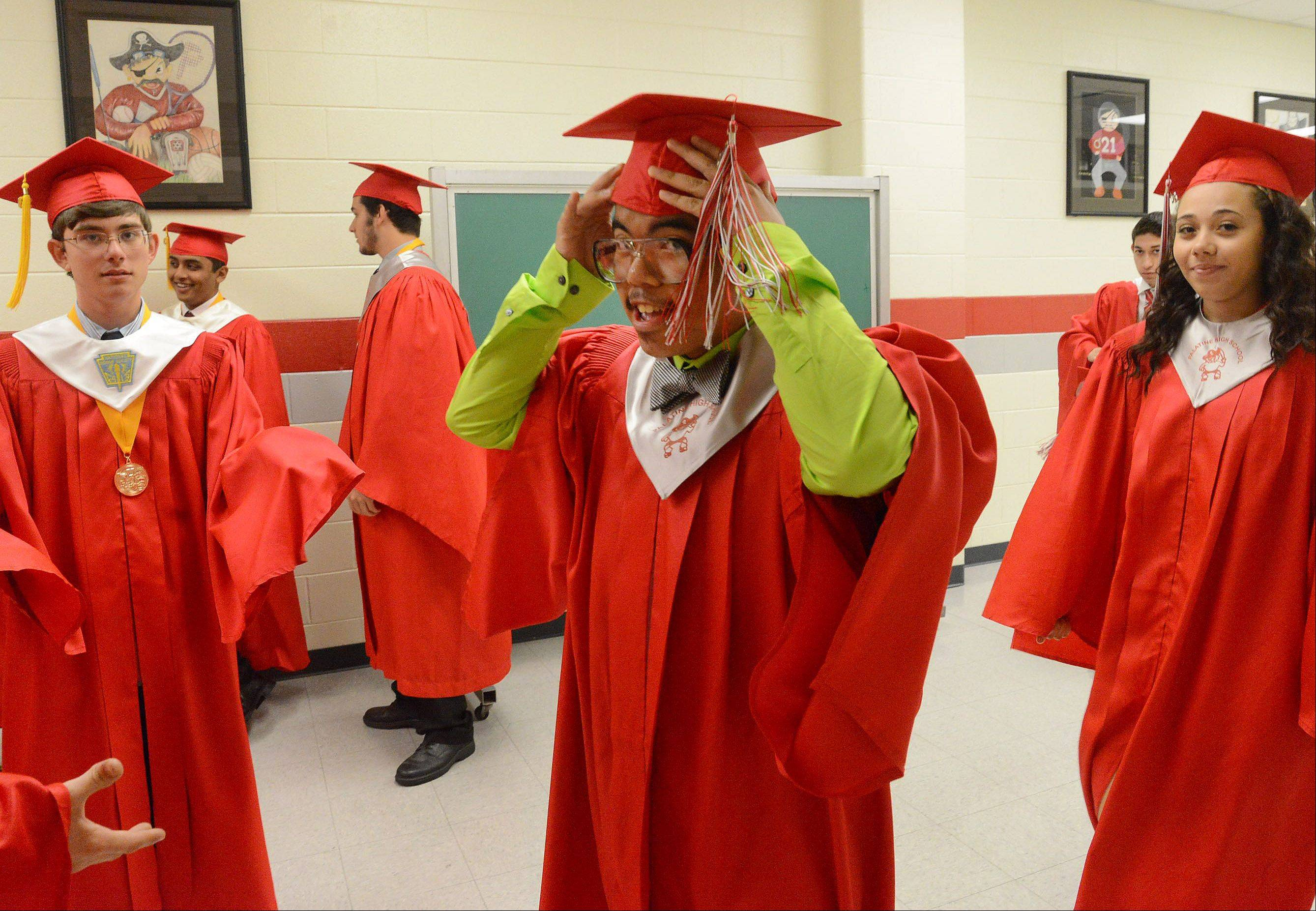 Oscar Rilloraza rushes to get to his place in line before the Palatine High School graduation.