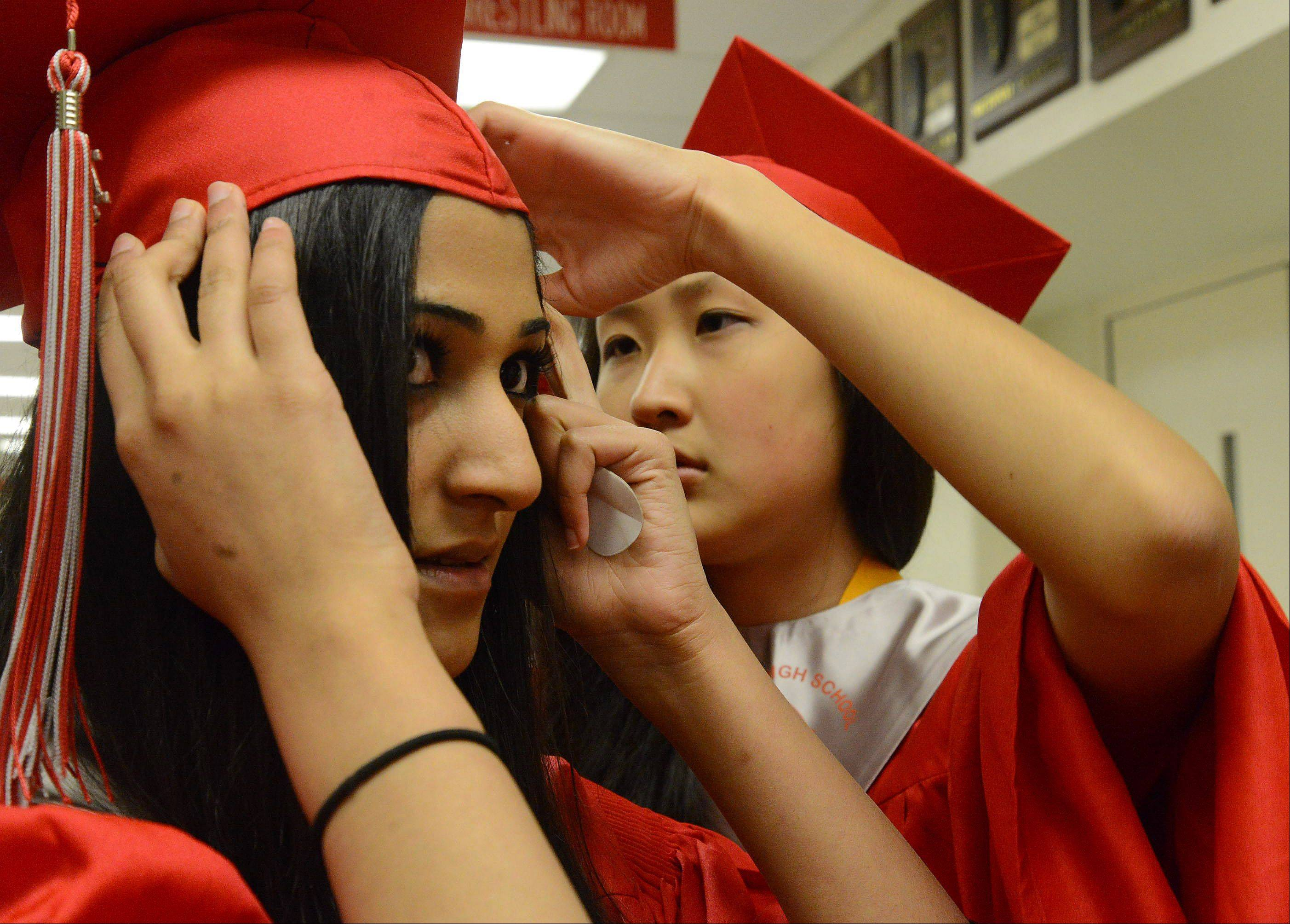 Aasia Bhatti, left, gets help with her mortar board from Alice Cho, before the Palatine High School graduation.
