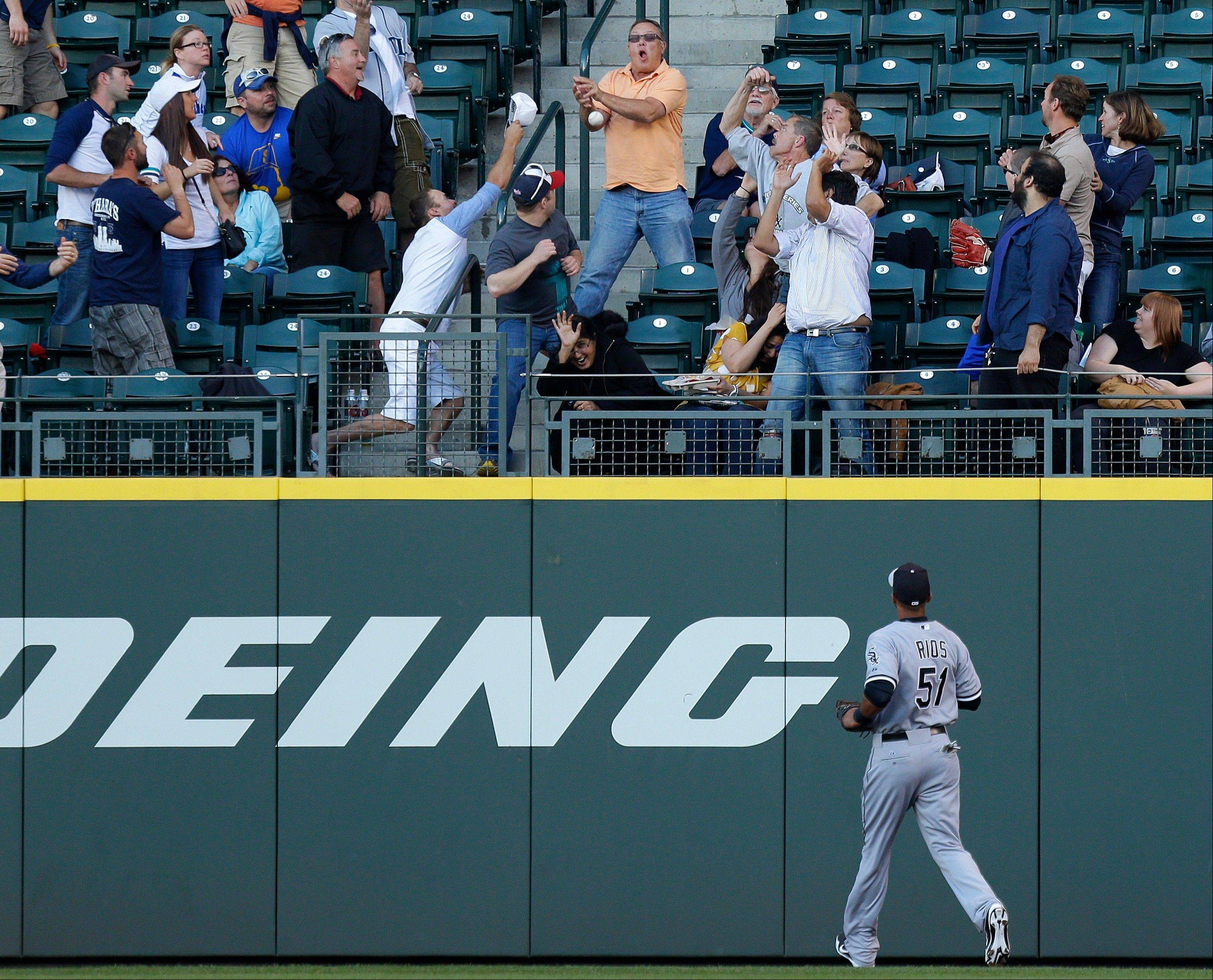 White Sox right fielder Alex Rios can only watch as fans attempt to catch a two-run home run hit by Seattle Mariners' Raul Ibanez in the third inning of a baseball game, Monday, June 3, 2013, in Seattle.