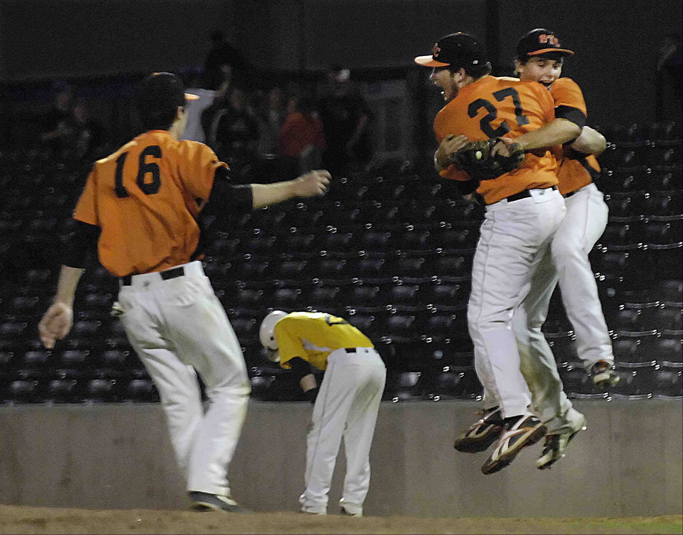 St. Charles East pitcher Matt Starai and first baseman Brian Sobieski hug in midair as teammate Sean Dunne approaches and Jacobs' Jon Berndt reacts to grounding out to end the game Monday in the Class 4A supersectional at RiverHawks Stadium in Rockford. The Saints will advance to the state tournament this weekend.