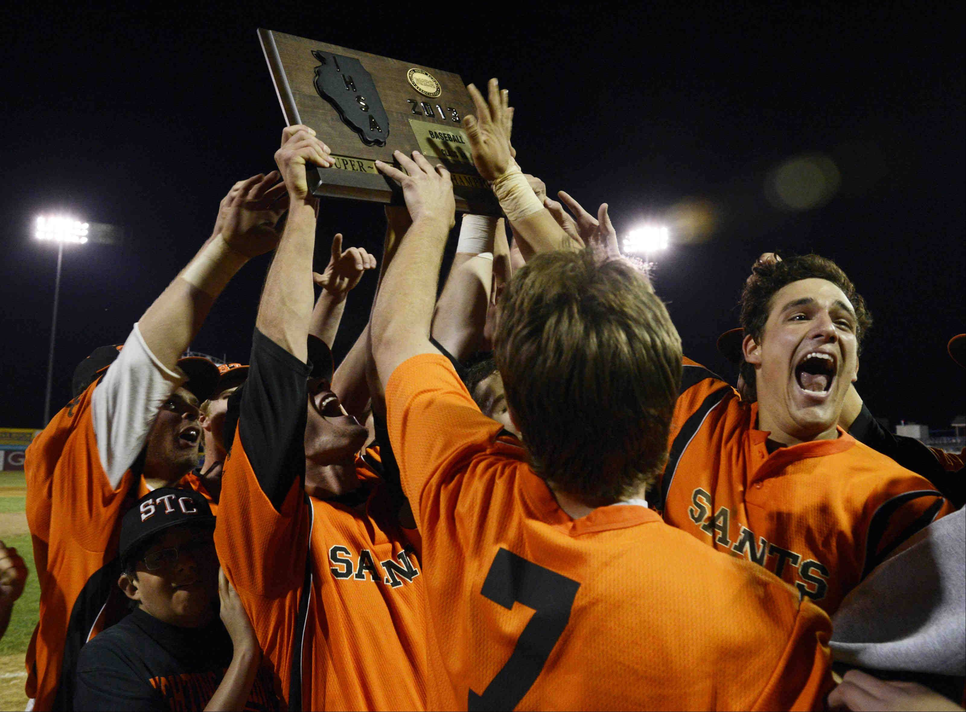 St. Charles East's Anthony Sciarrino turns to the crowd and yells as he reaches for the Class 4A supersectional plaque at RiverHawks Stadium in Rockford Monday. He had 4 RB's in the 7-2 win over Jacobs.
