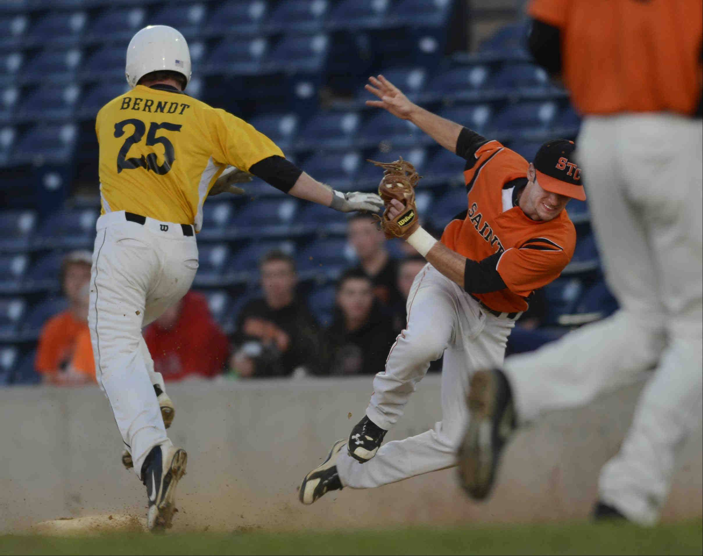 Jacobs' Jon Berndt collides with St. Charles East first baseman Jack Dellostritto Monday in the Class 4A supersectional at RiverHawks Stadium in Rockford. He was out on the bunt.