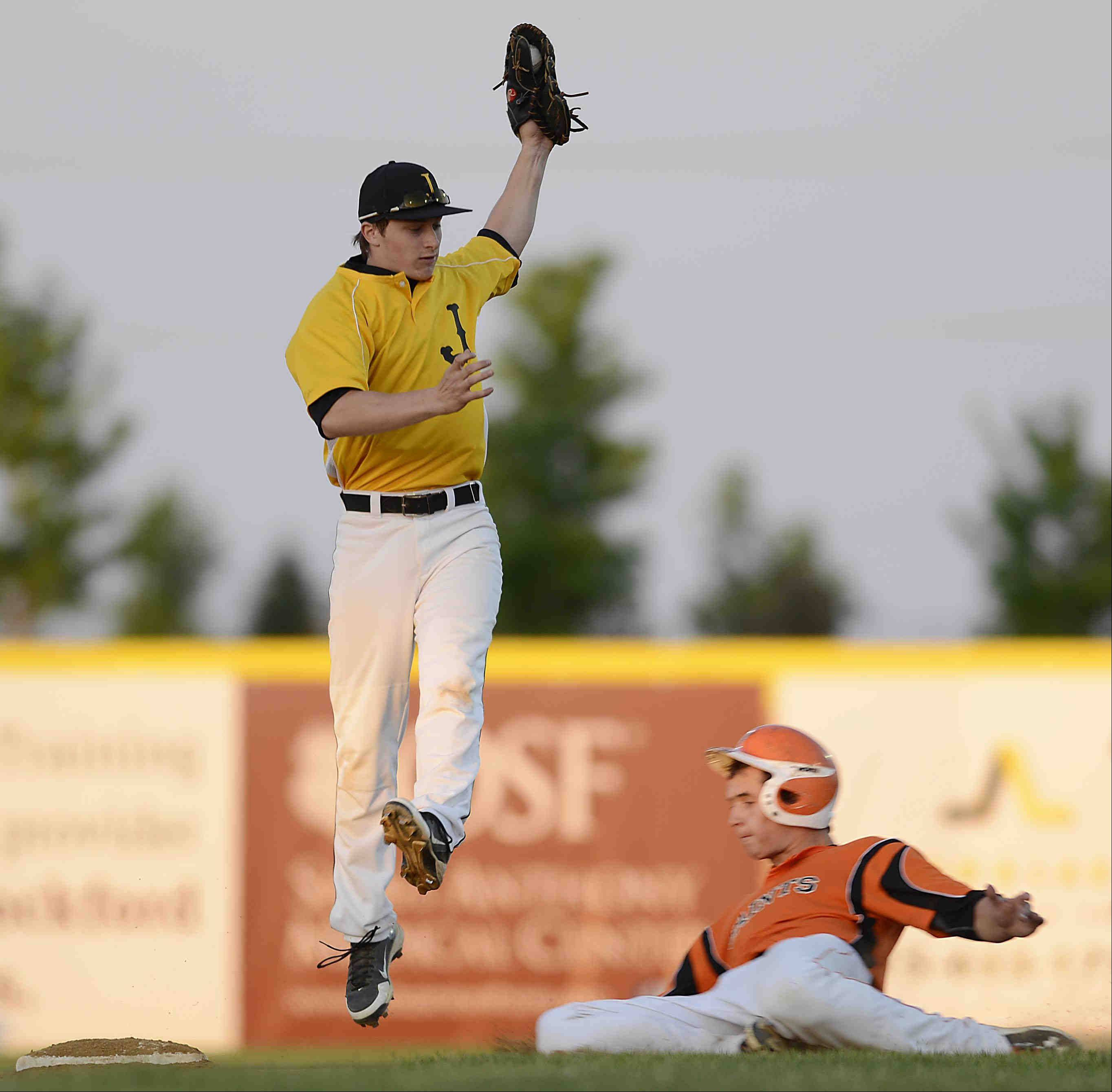 Jacobs' Grant Kale jumps to catch a high throw to second as St. Charles East's Brian Sobieski steals the bag Monday in the Class 4A supersectional at RiverHawks Stadium in Rockford.