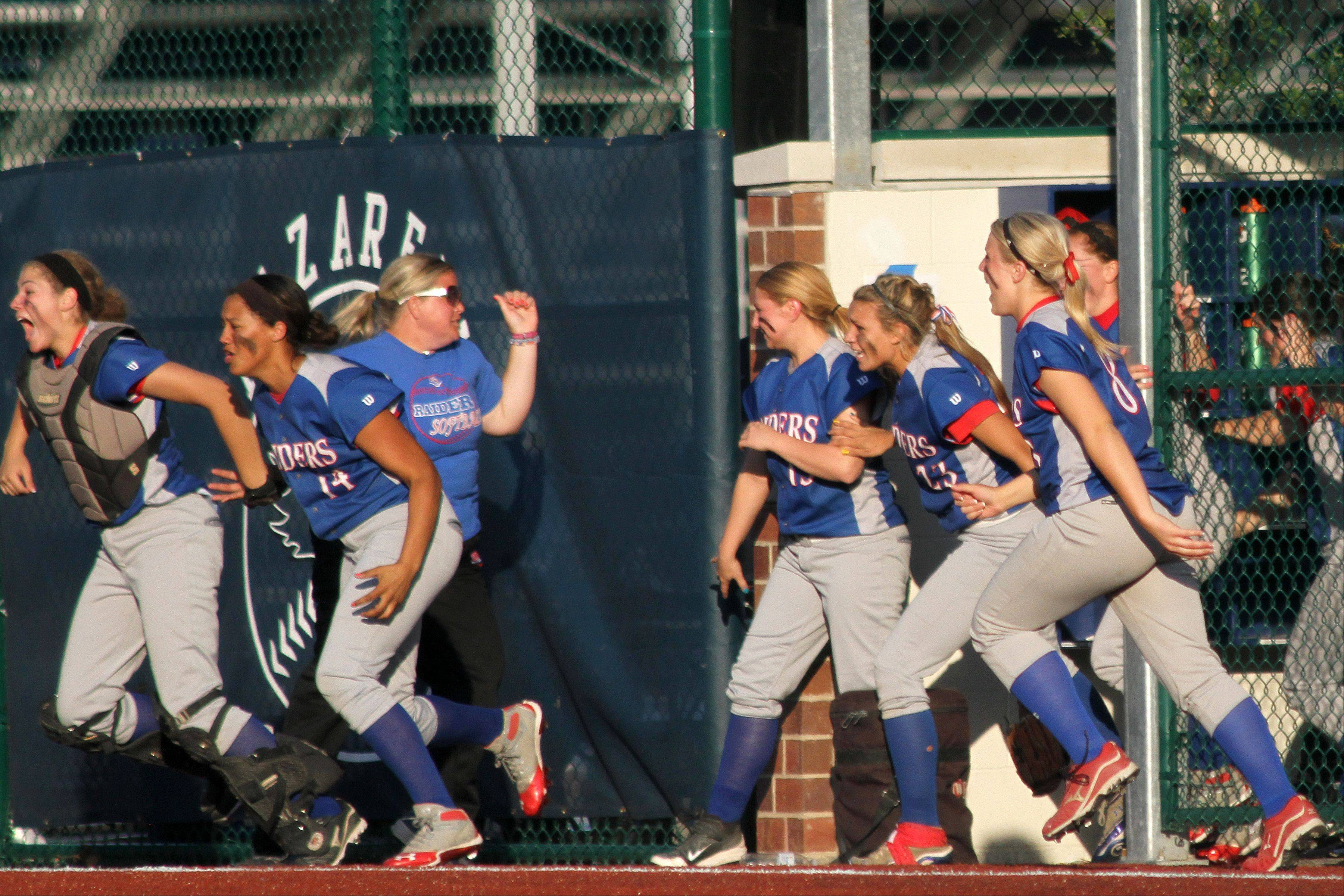 Glenbard South High School girls softball team runs from their dugout after beating Fenwick High School 2-1 in the 11th inning at the Class 3A Girls Softball Super-sectional game on Monday, June 3, 2013 at Nazareth Academy in LaGrange Park.