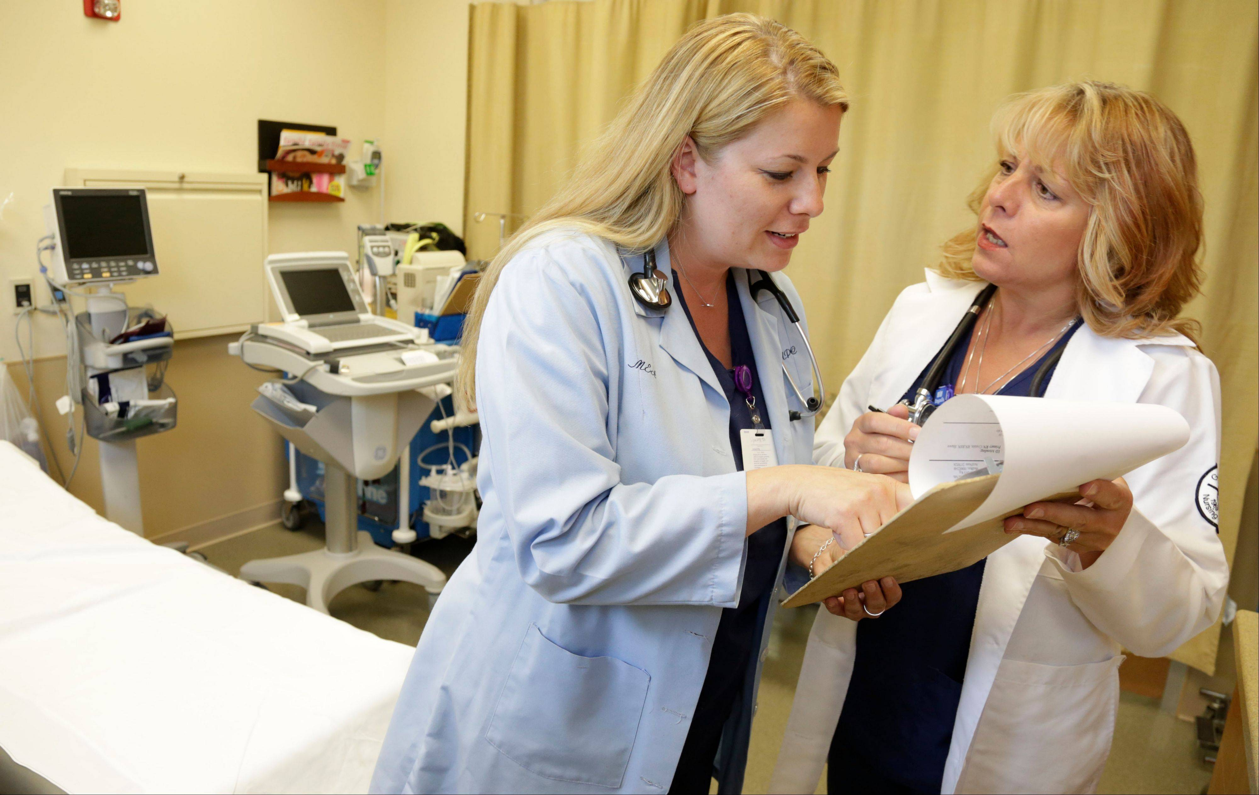 Nurse practitioners Michele Knappe, left, and Julie Zimmer go over a patient's chart Tuesday at Ingalls Family Care Center in Flossmoor. Illinois lawmakers this spring rebuffed a variety of proposals that would have given more authority to nurses ahead of a surge of patients newly insured under President Obama's health law.