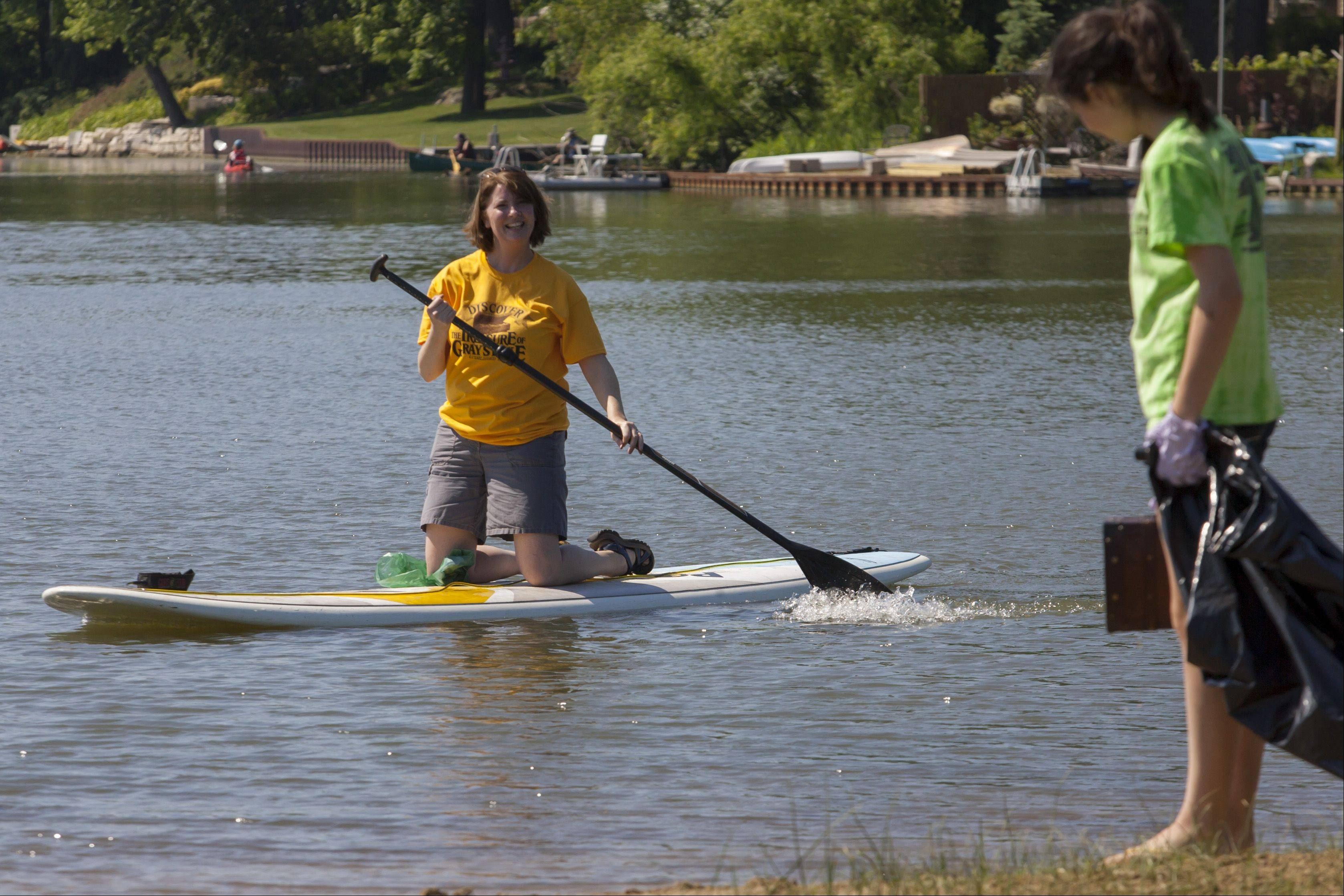 During last year's Grays Lake shoreline cleanup and treasure hunt, Annie Caliendo lands her paddle board so that her daughter, Hope, can have a turn. Hope found one of five treasure chests hidden around the lake as a prize for helping reduce trash.