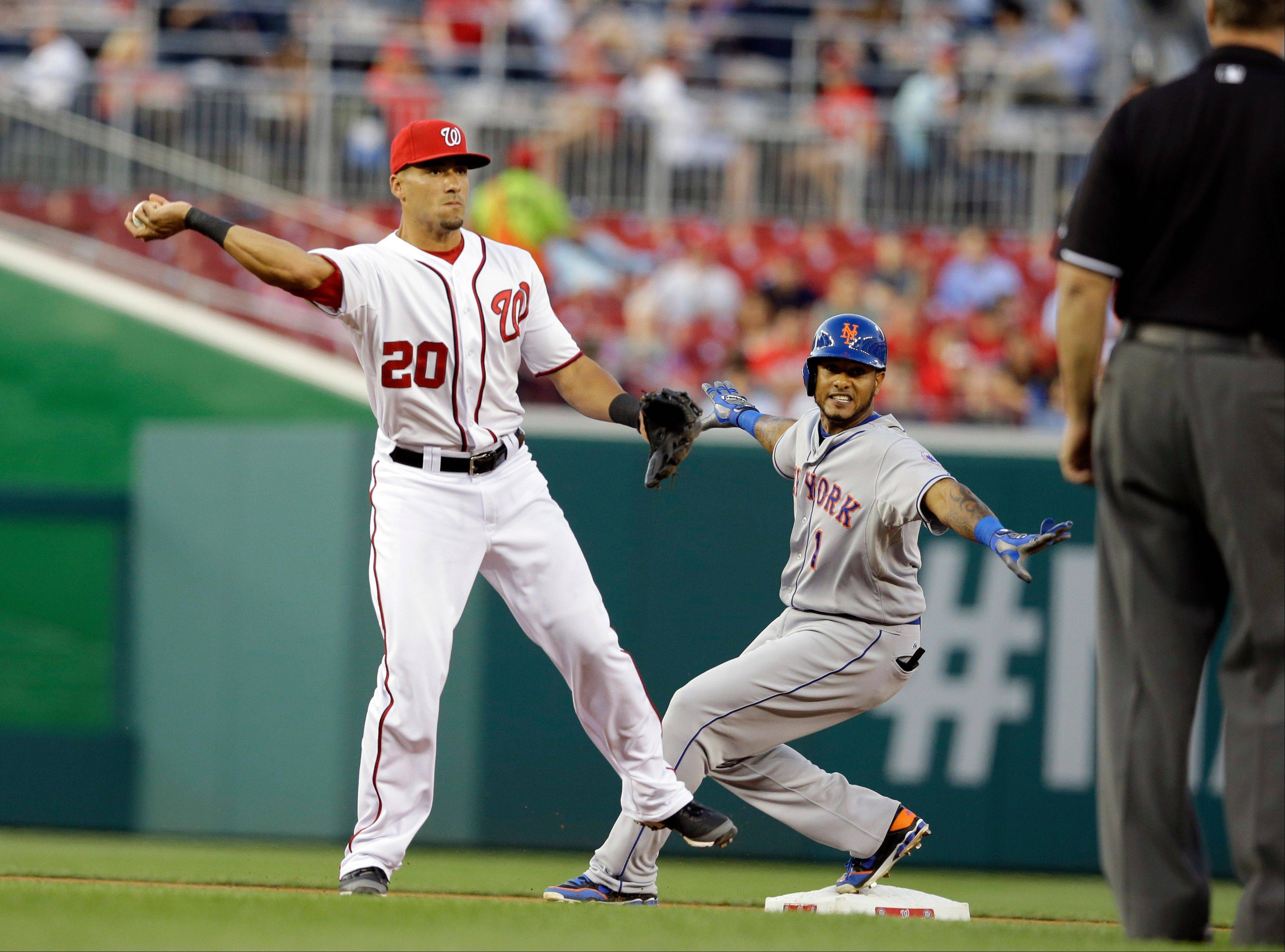 Washington Nationals shortstop Ian Desmond (20) checks his throw to first as New York Mets� Jordany Valdespin (1) is safe at second during the fifth inning of a baseball game at Nationals Park Tuesday in Washington.