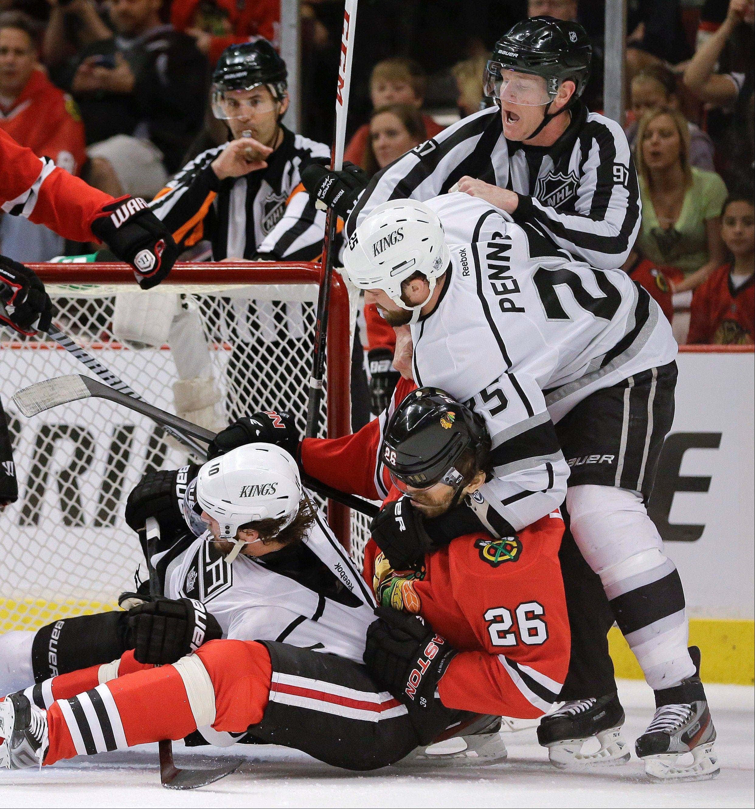 Los Angeles Kings left wing Dustin Penner (25) grabs Chicago Blackhawks center Michal Handzus (26), who pulls down Los Angeles Kings center Mike Richards (10) during a fight in the first period of Game 1 of the NHL hockey Stanley Cup Western Conference finals Saturday in Chicago. Richards has been pulled from the Kings' lineup for Game 3.