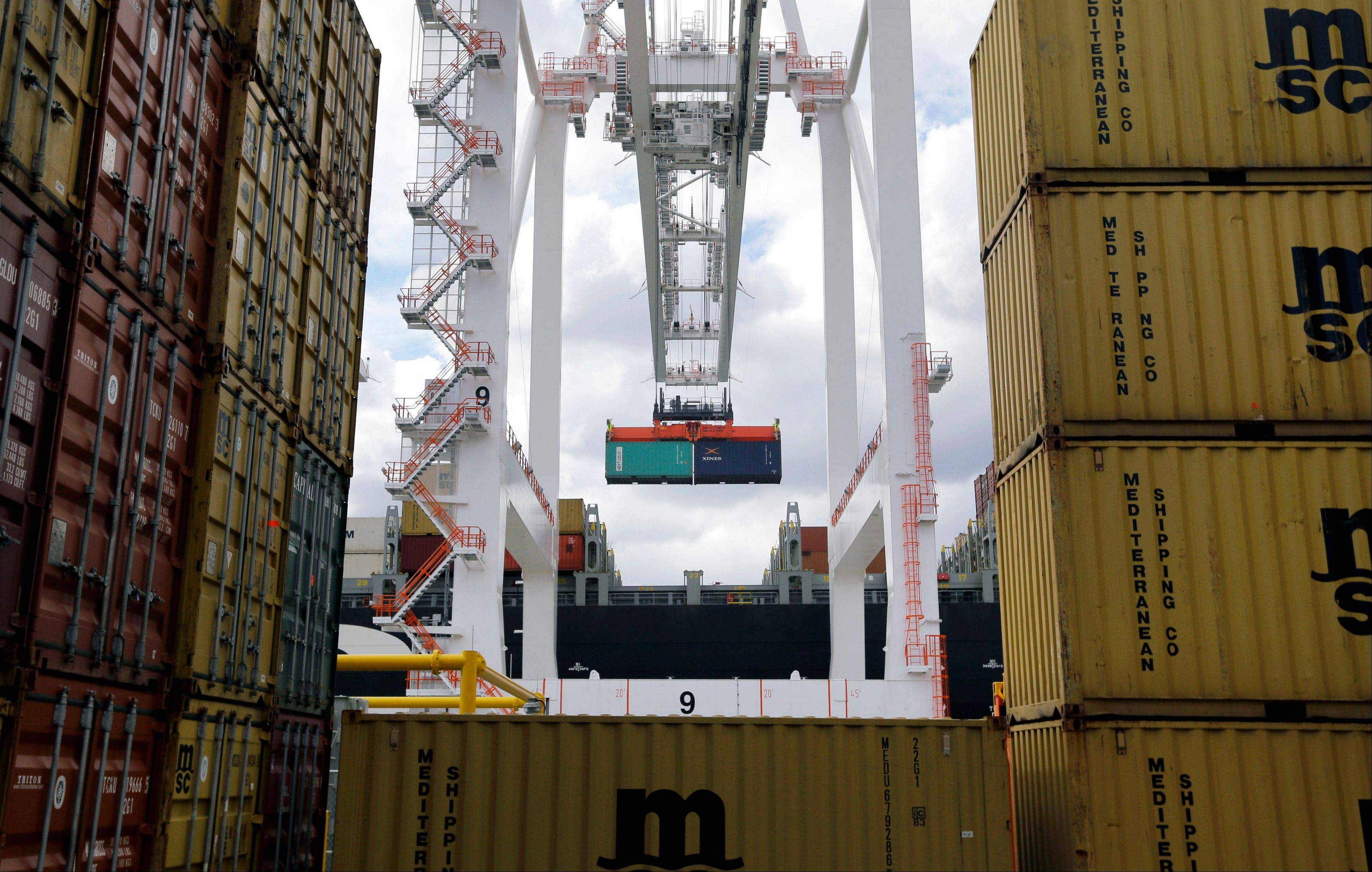 A crane removes a container from a ship at the Port of Baltimore's Seagirt Marine Terminal in Baltimore. The U.S. trade deficit widened in April, as demand for foreign cars, cell phones and other imported goods outpaced growth in U.S. exports.