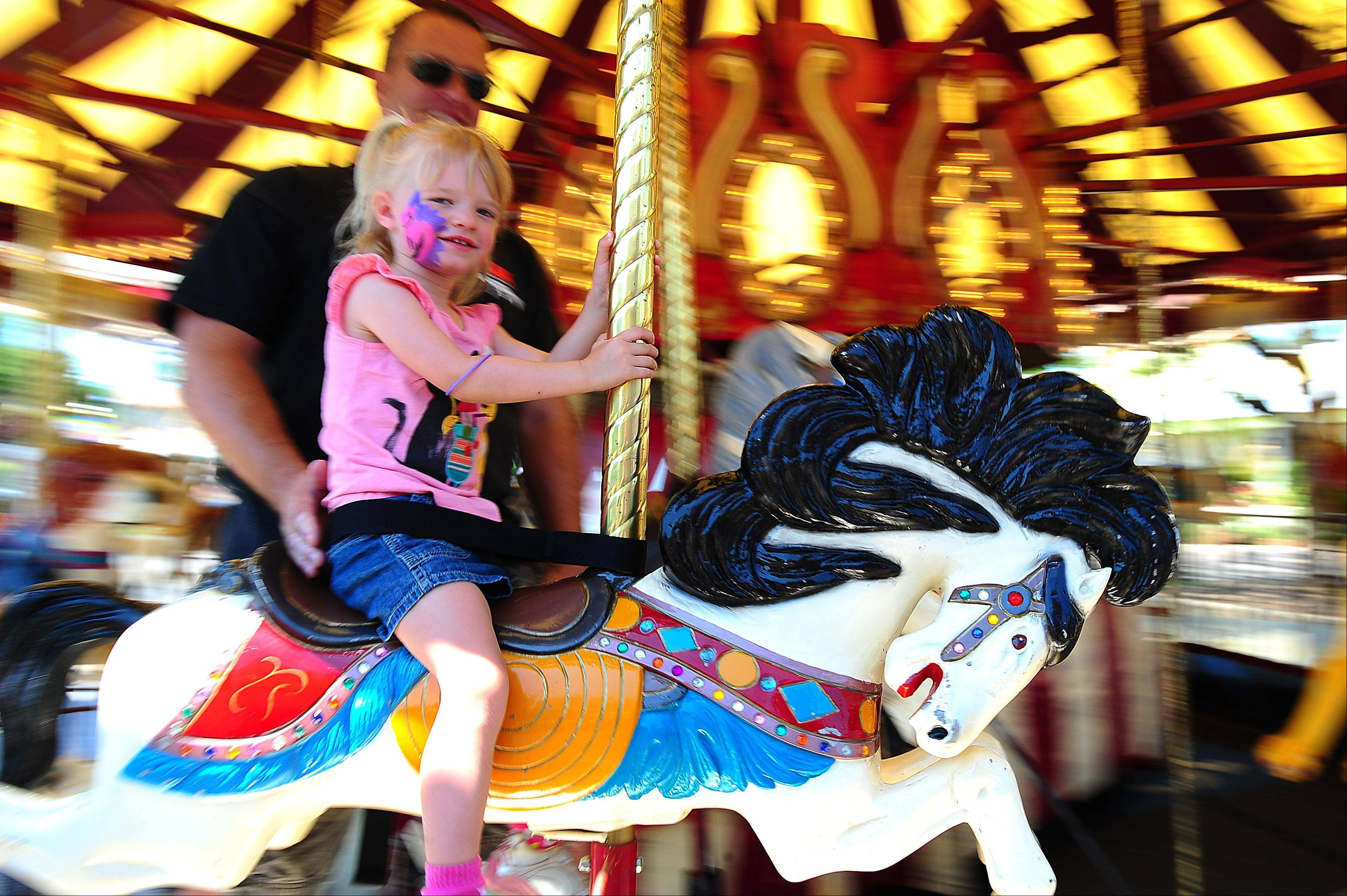 Brad Bilut rides the merry-go-round with his daughter Jenna during last year's Pride of the Fox RiverFest, this year renamed City of St. Charles RiverFest.
