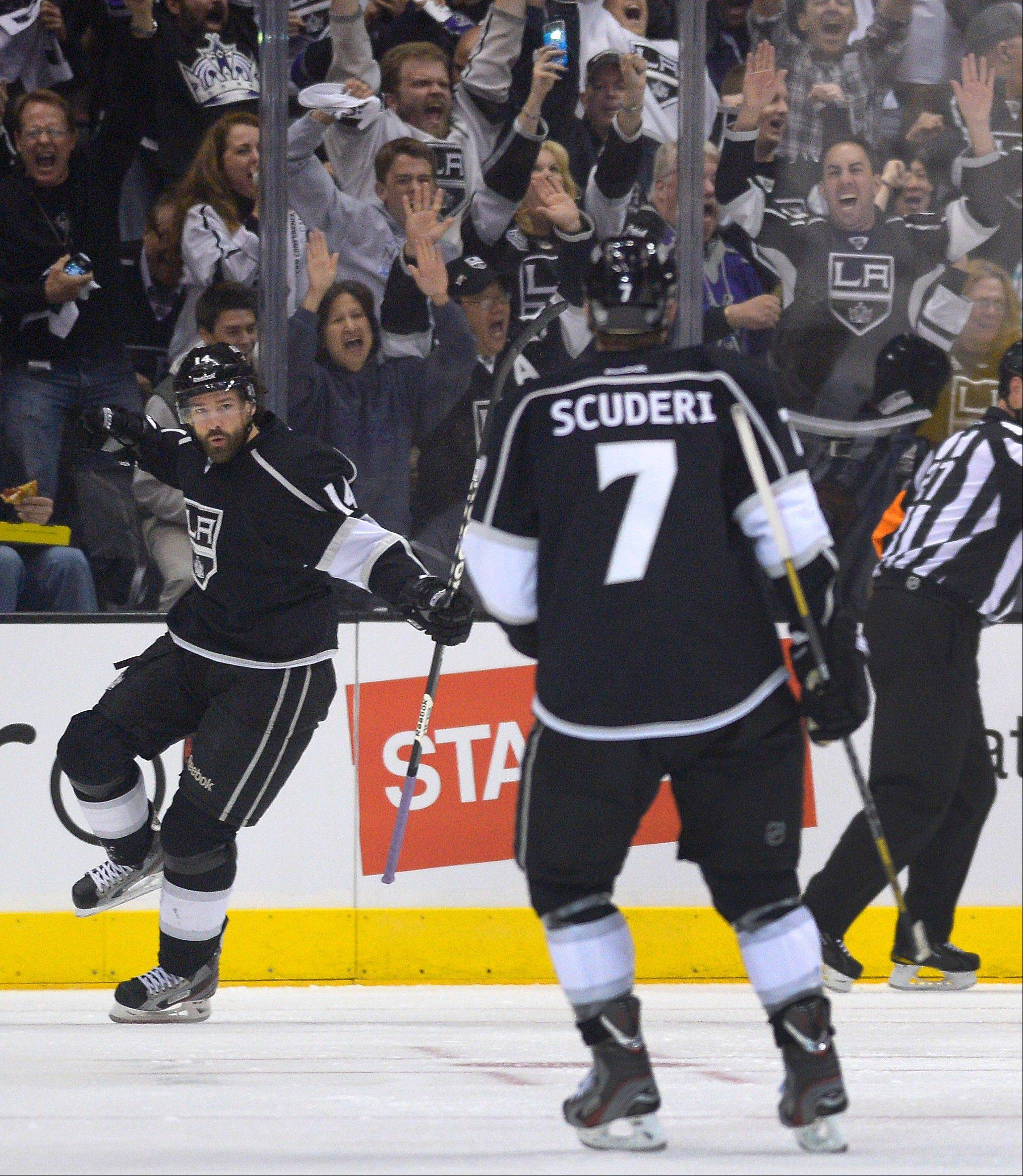 Los Angeles Kings right wing Justin Williams (14) celebrates in front of defenseman Rob Scuderi (7) after scoring a goal against the Chicago Blackhawks during the first period in Game 3 of the NHL hockey Stanley Cup playoffs Western Conference finals, Tuesday, June 4, 2013, in Los Angeles.