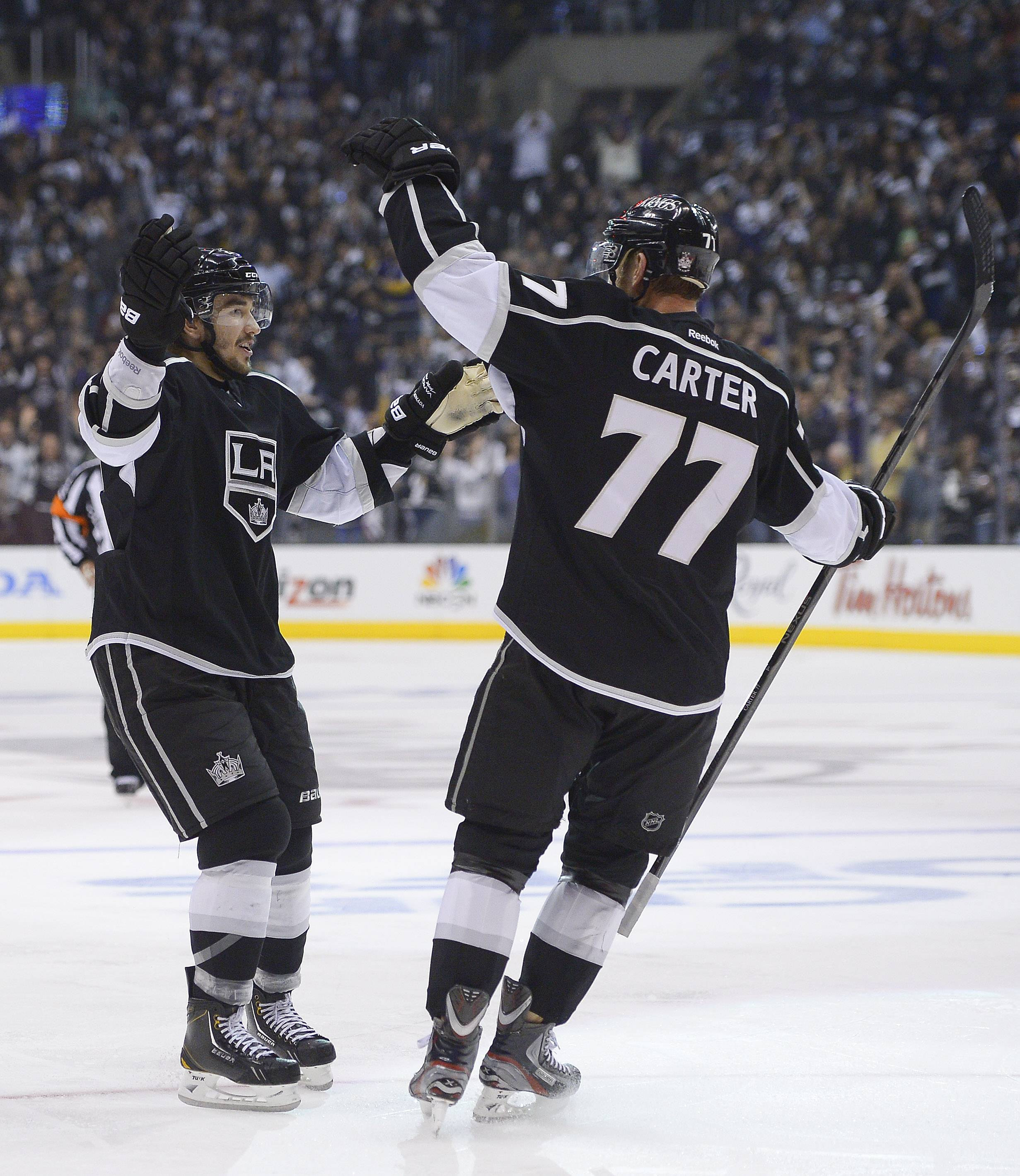 Los Angeles Kings defenseman Slava Voynov, left, celebrates with center Jeff Carter (77) after scoring a goal against the Chicago Blackhawks during the second period in Game 3 of the NHL hockey Stanley Cup playoffs Western Conference finals, Tuesday, June 4, 2013, in Los Angeles.