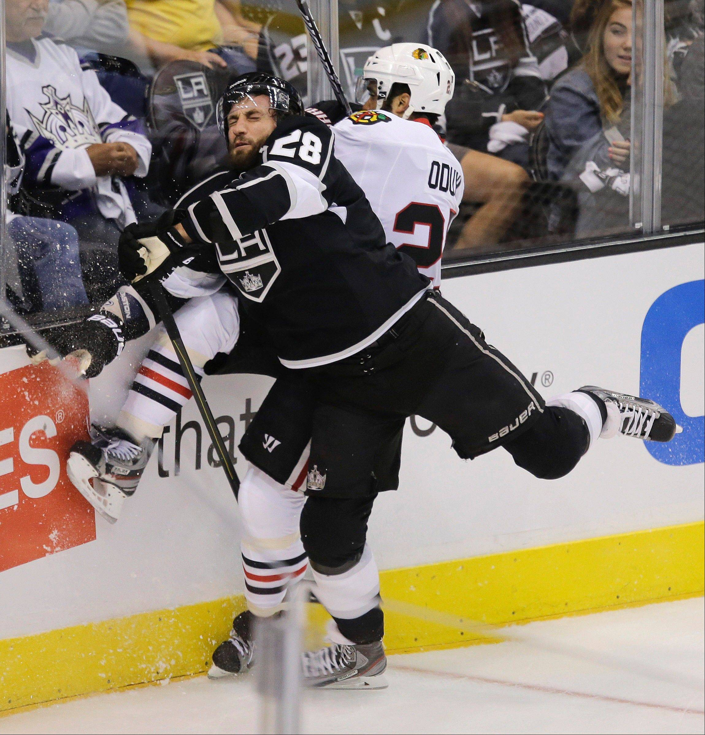 Los Angeles Kings center Jarret Stoll (28) collides with Chicago Blackhawks defenseman Johnny Oduya (27) during the first period of Game 3 of the NHL hockey Stanley Cup playoffs Western Conference finals, Tuesday, June 4, 2013, in Los Angeles.